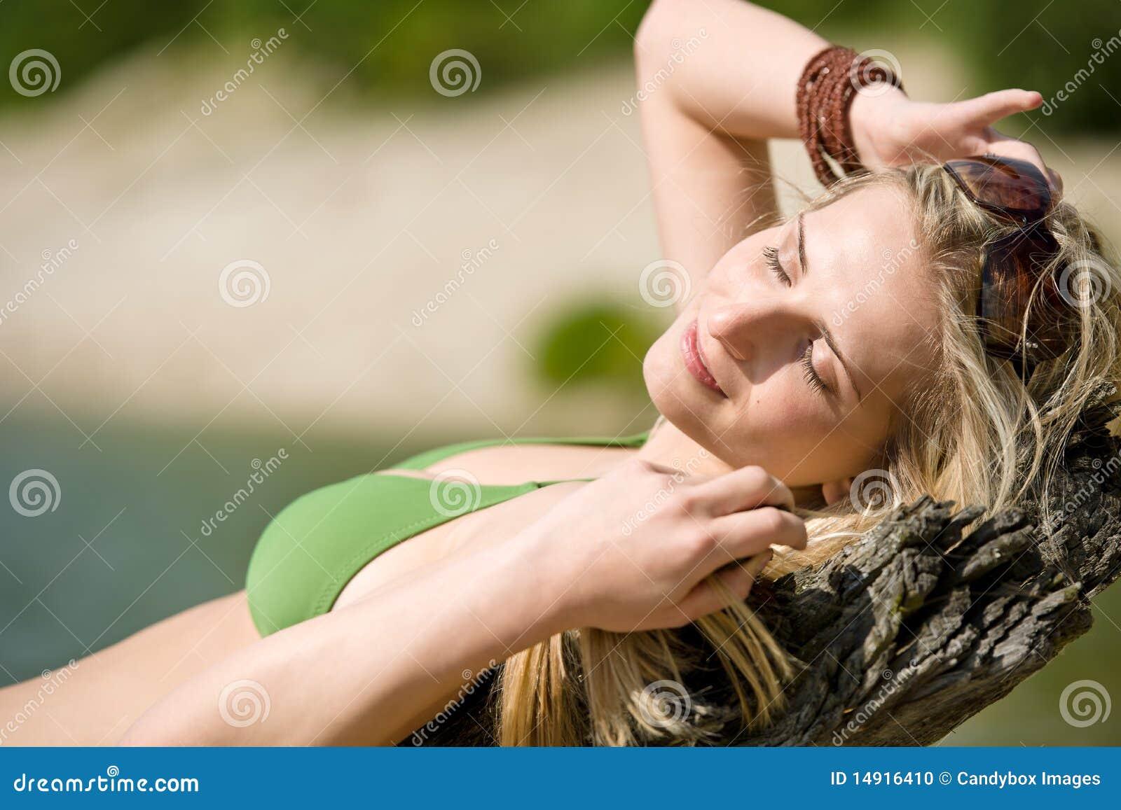 Le femme blond détendent dans le bikini au lac