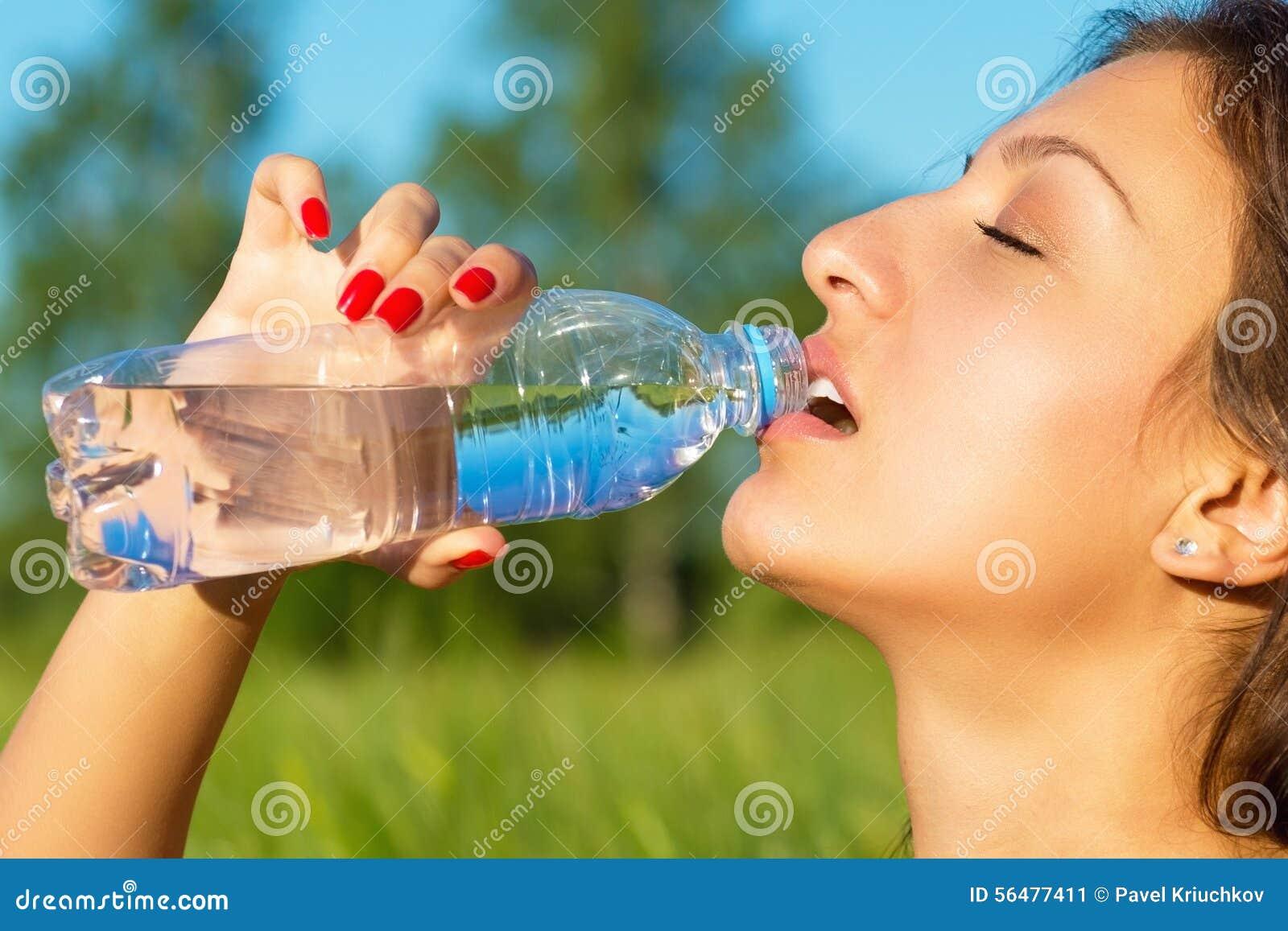 Le femme boit l eau d une bouteille