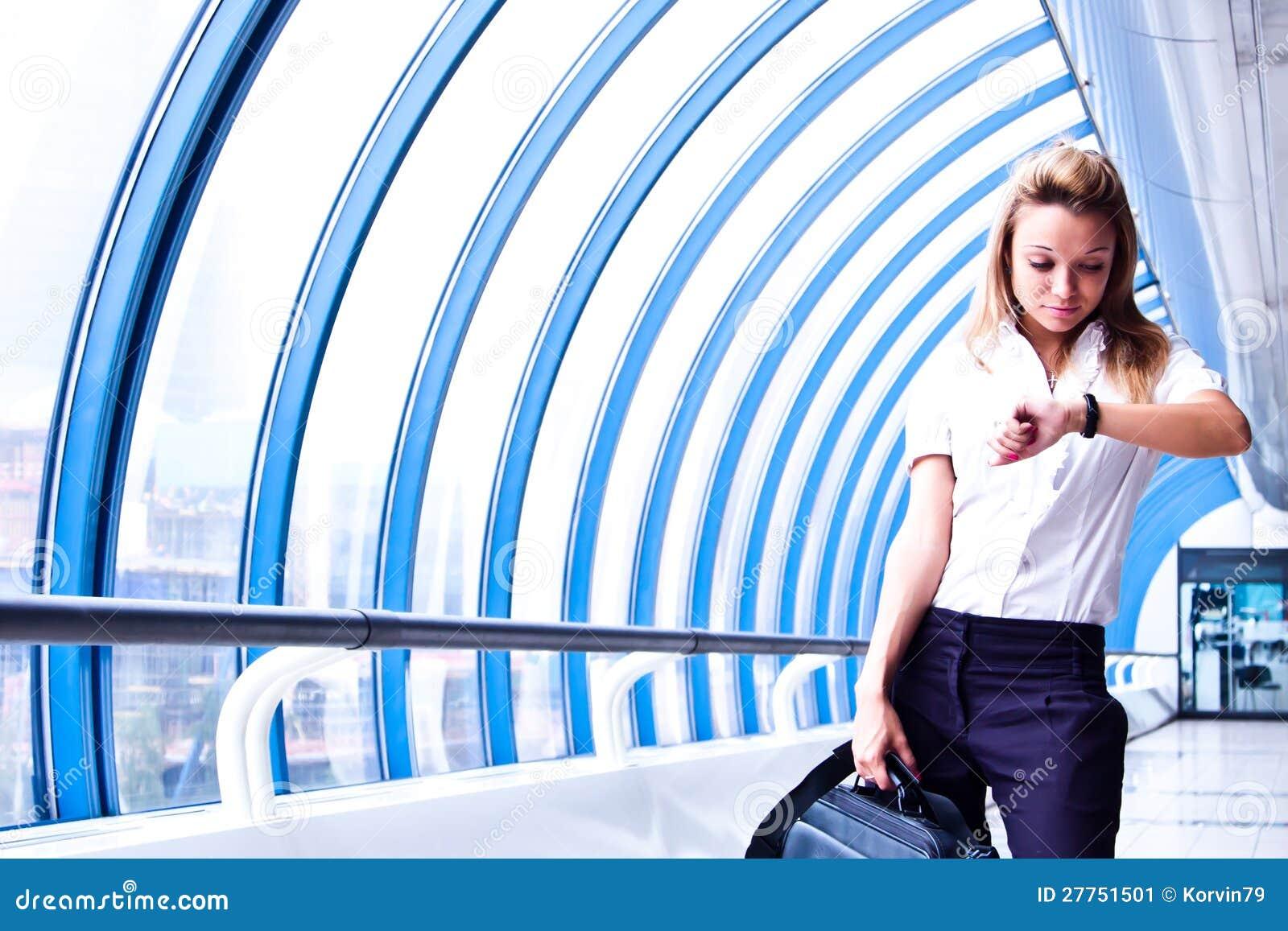 Le femme d affaires regarde l horloge
