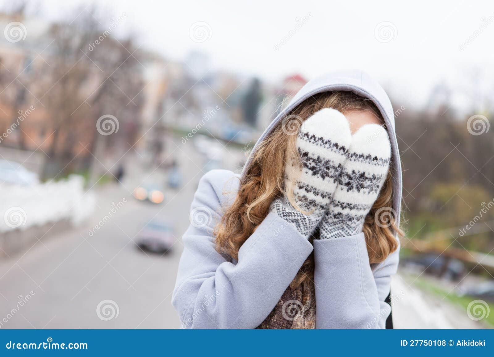 Le femme en hiver vêtx le visage couvert avec des mitaines