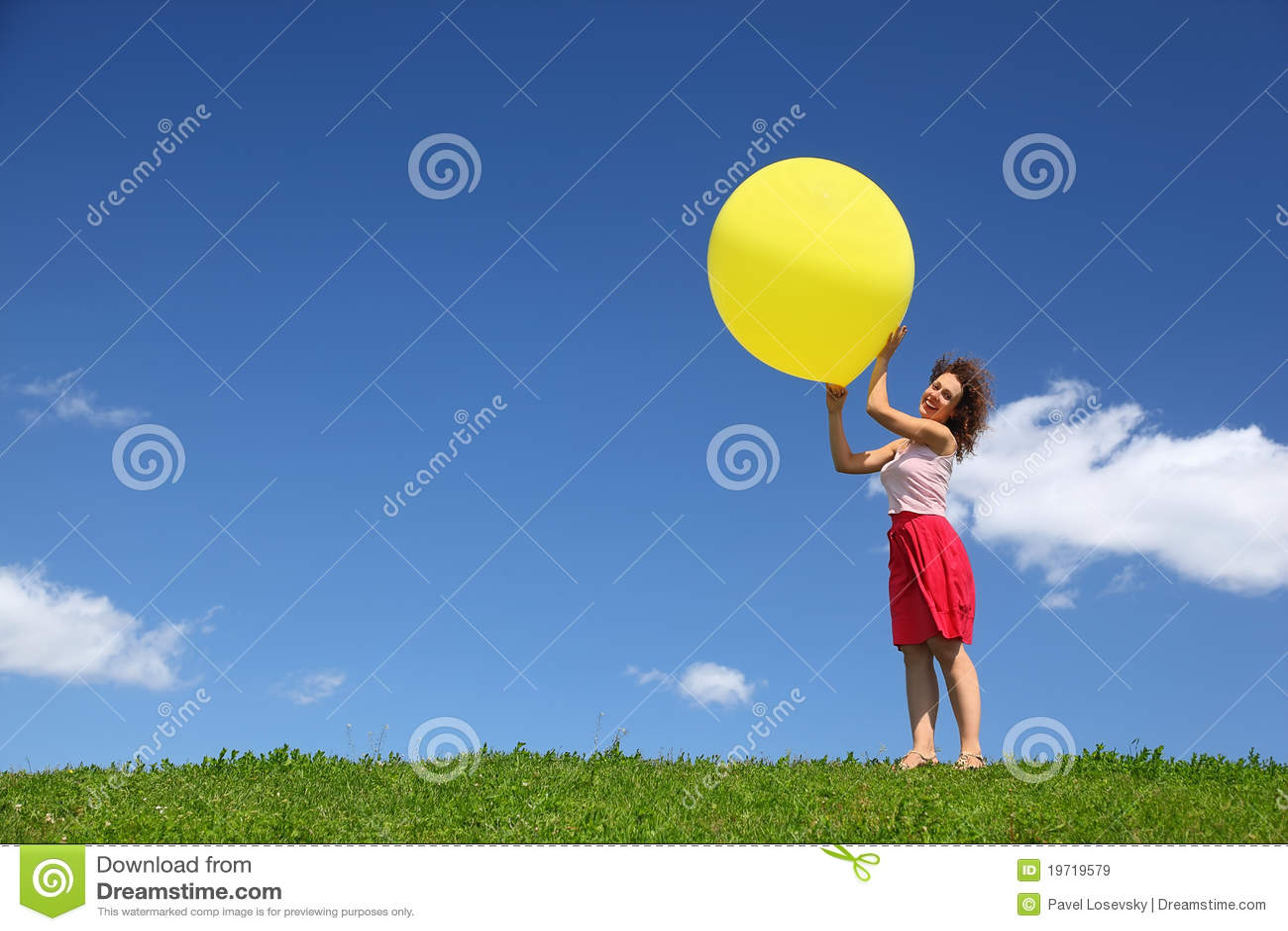 Le femme retient la grande bille dans des mains sur le vent