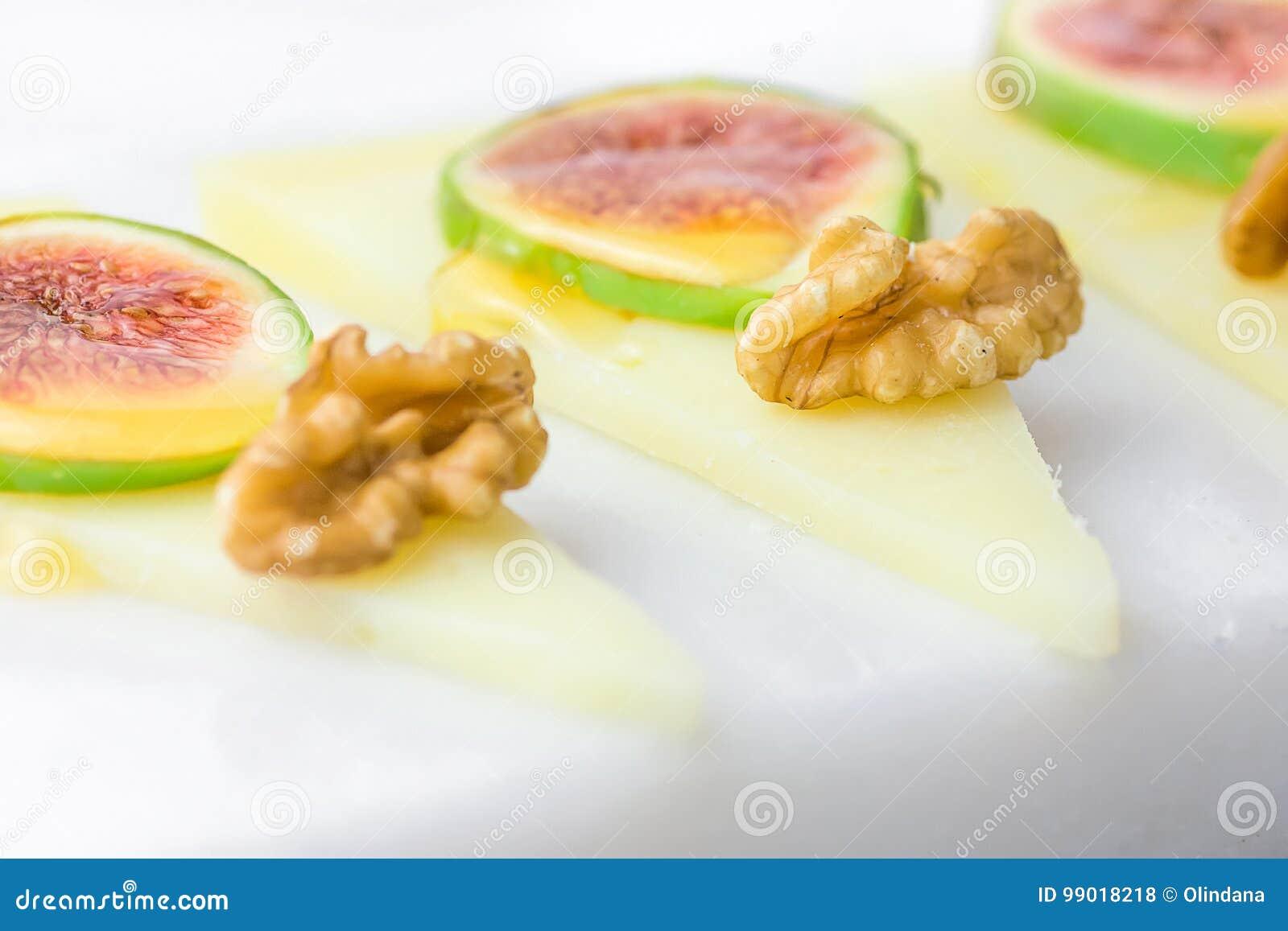 Le fette di formaggio di capra spagnolo semiduro curato con le noci, fichi maturi hanno piovigginato con miele sul bordo di marmo