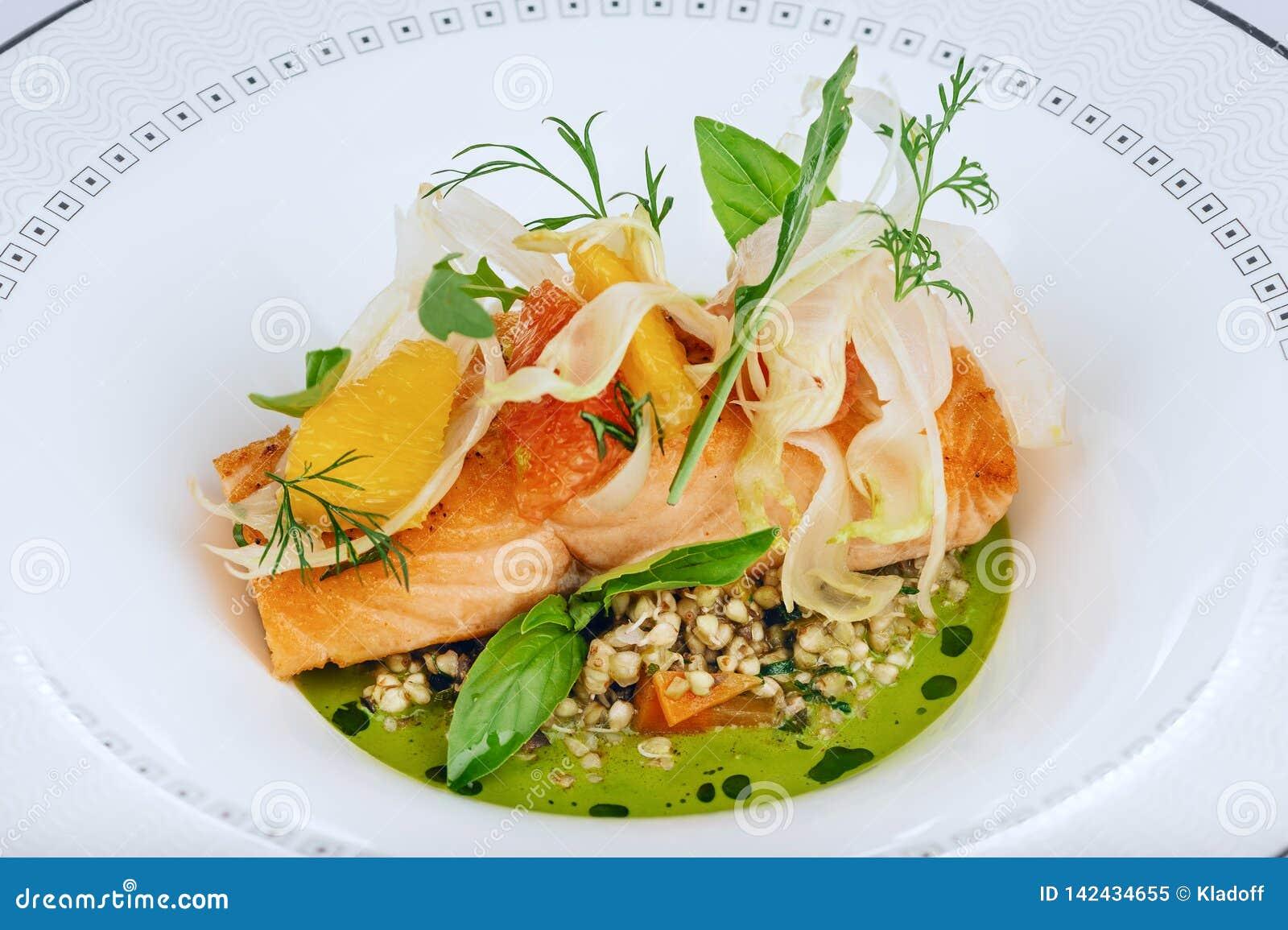 Le filet de poissons rouge saumoné a fait cuire avec le plan rapproché frais de feuilles de salade verte d isolement du plat blan