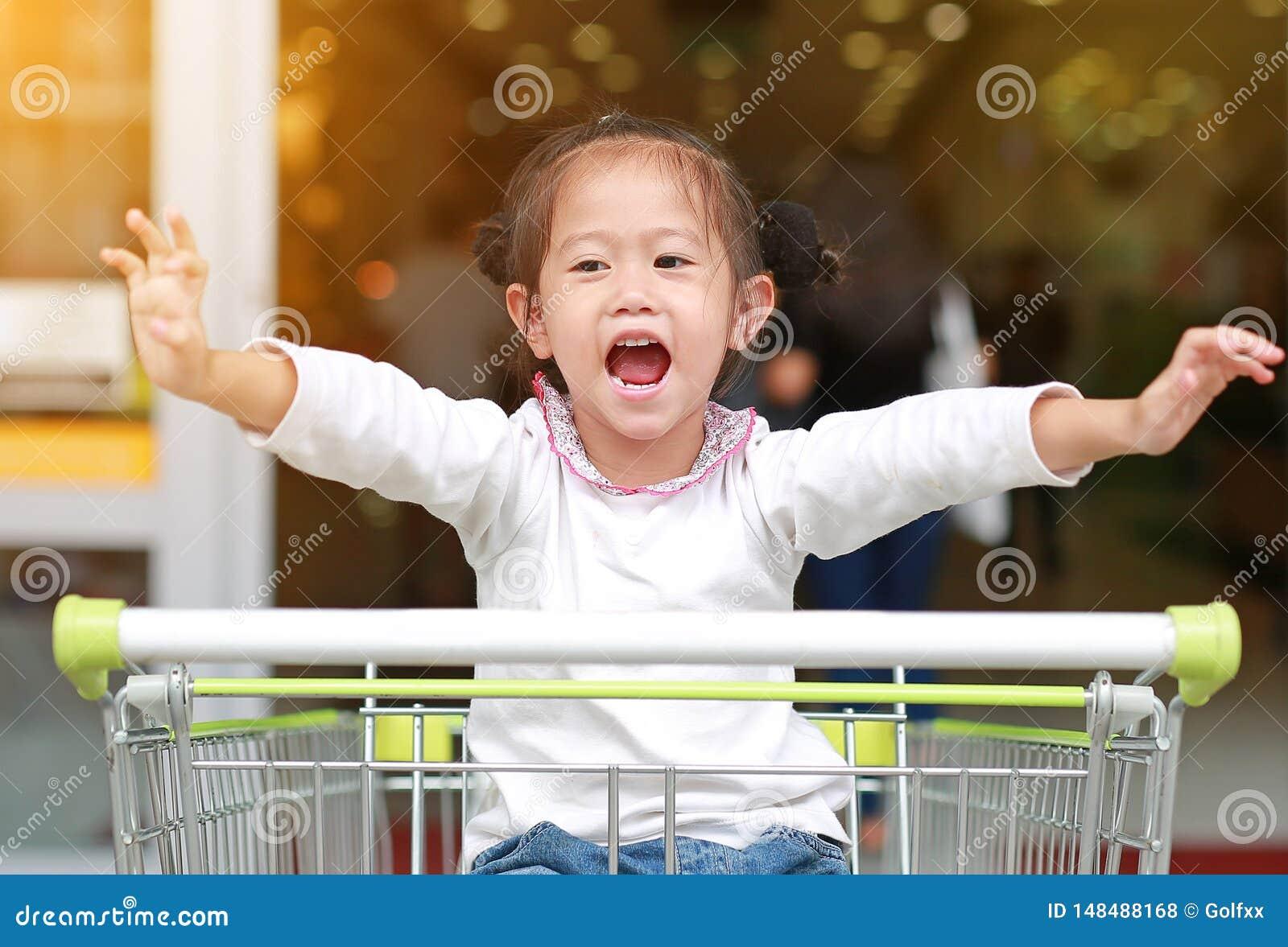 Le flickan f?r litet barn som sitter i sp?rvagnen under familjshopping i marknaden