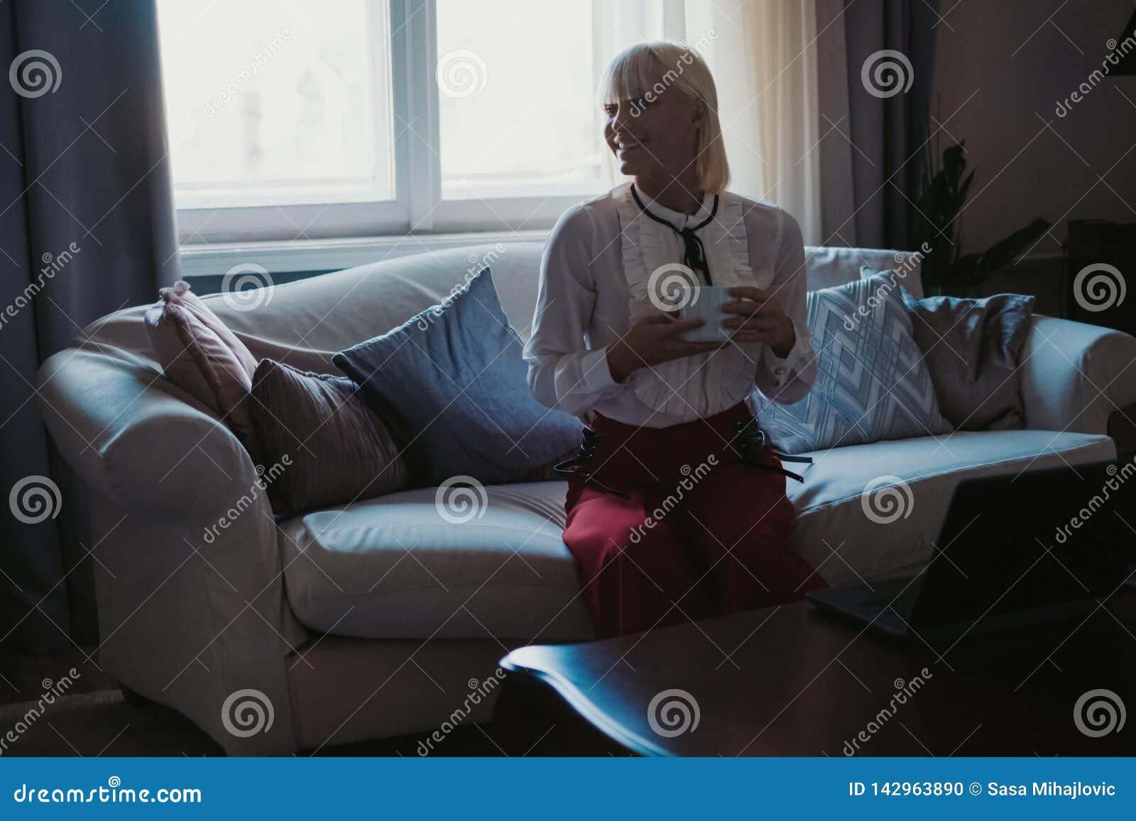 Le flickan som dricker kaffe på soffan vid fönstret