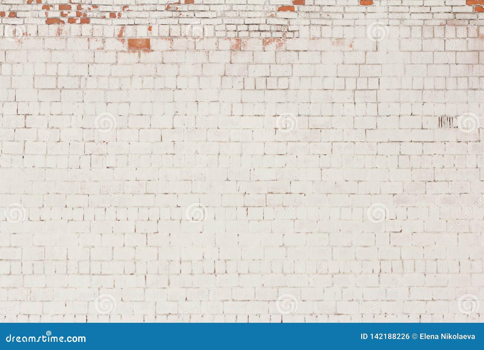Le fond de brique, vieux mur de briques a peint blanc et avec tombé le plâtre