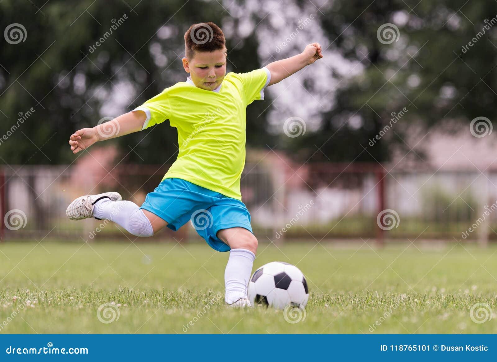 Le football de coup de pied de garçon sur le champ de sports