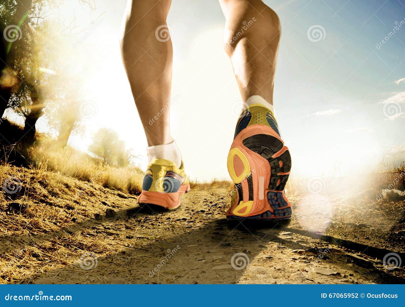 Le forti gambe e scarpe dello sport equipaggiano pareggiare nell allenamento di addestramento di forma fisica fuori dalla strada