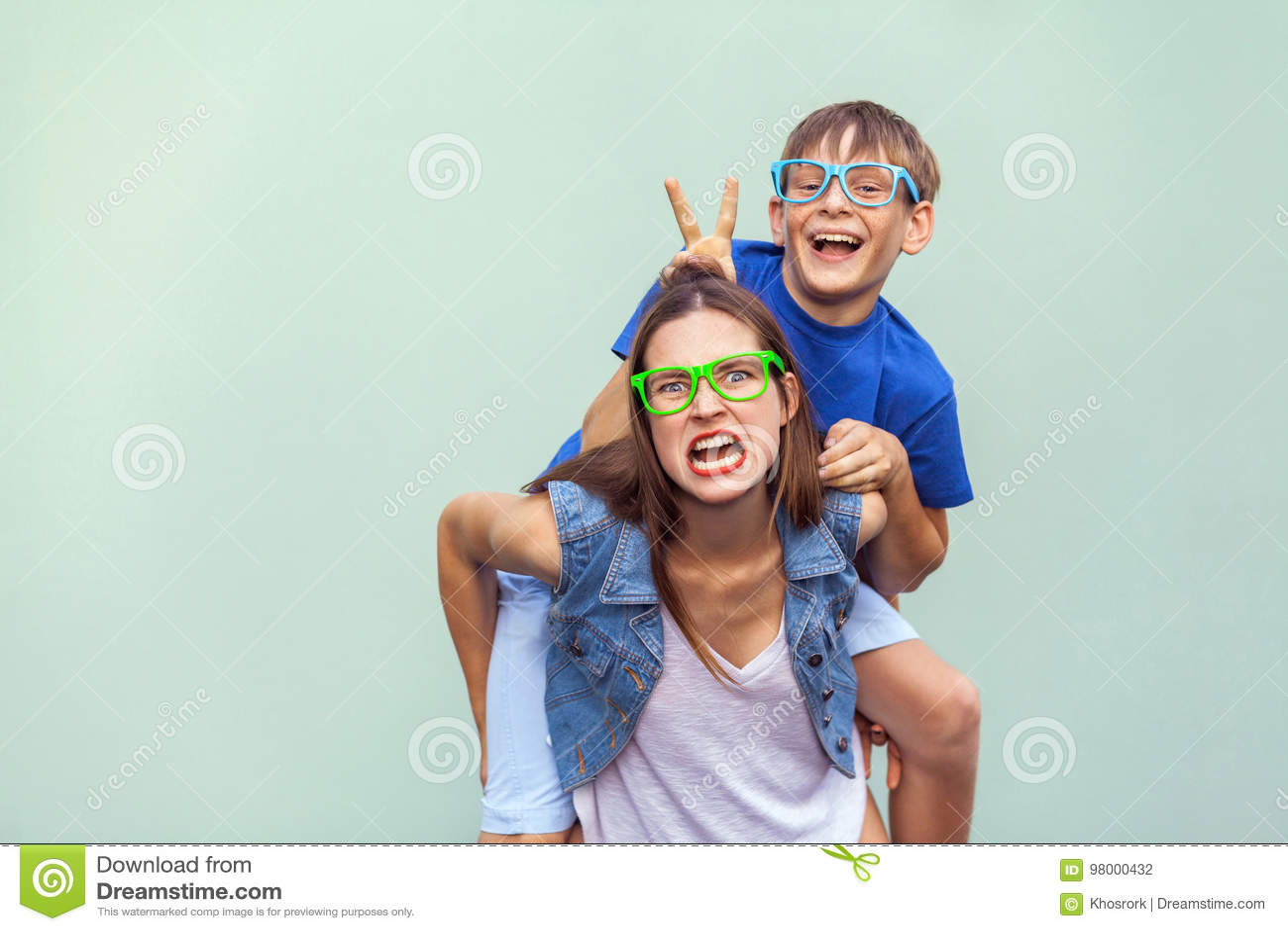 Le frère couvert de taches de rousseur s est élevé au dos d une soeur mignonne plus âgée Faisant le visage fou drôle et regarder