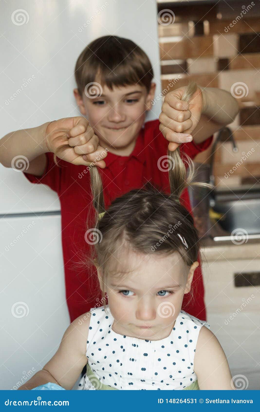 Le frère et la soeur dans la cuisine et le garçon tire la fille par les queues