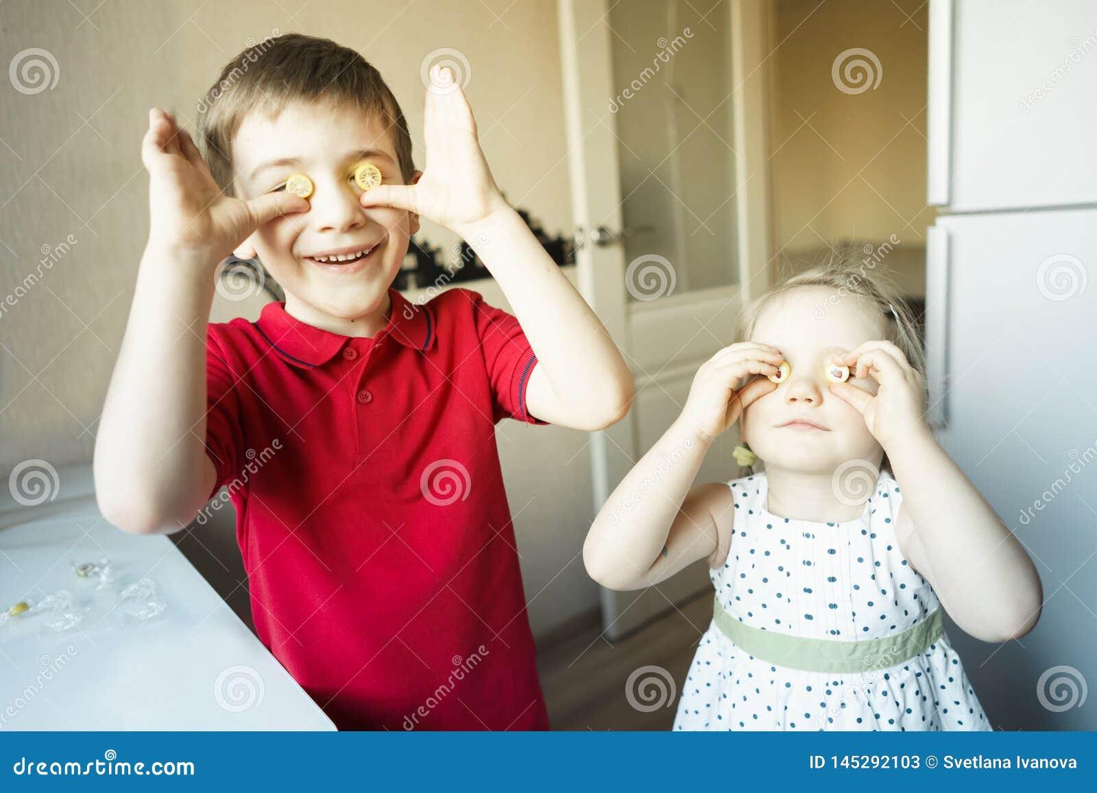 Le frère et la soeur drôles ferment leurs yeux avec la sucrerie comme des verres