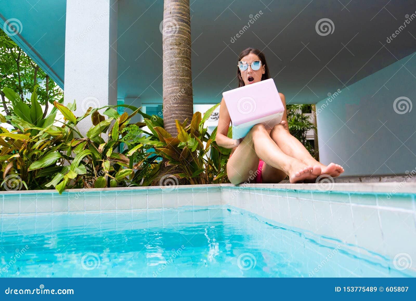 Le free lance femminili si siedono dallo stagno e gettano il computer portatile nell acqua la ragazza è oltraggiata, sorpreso, sp