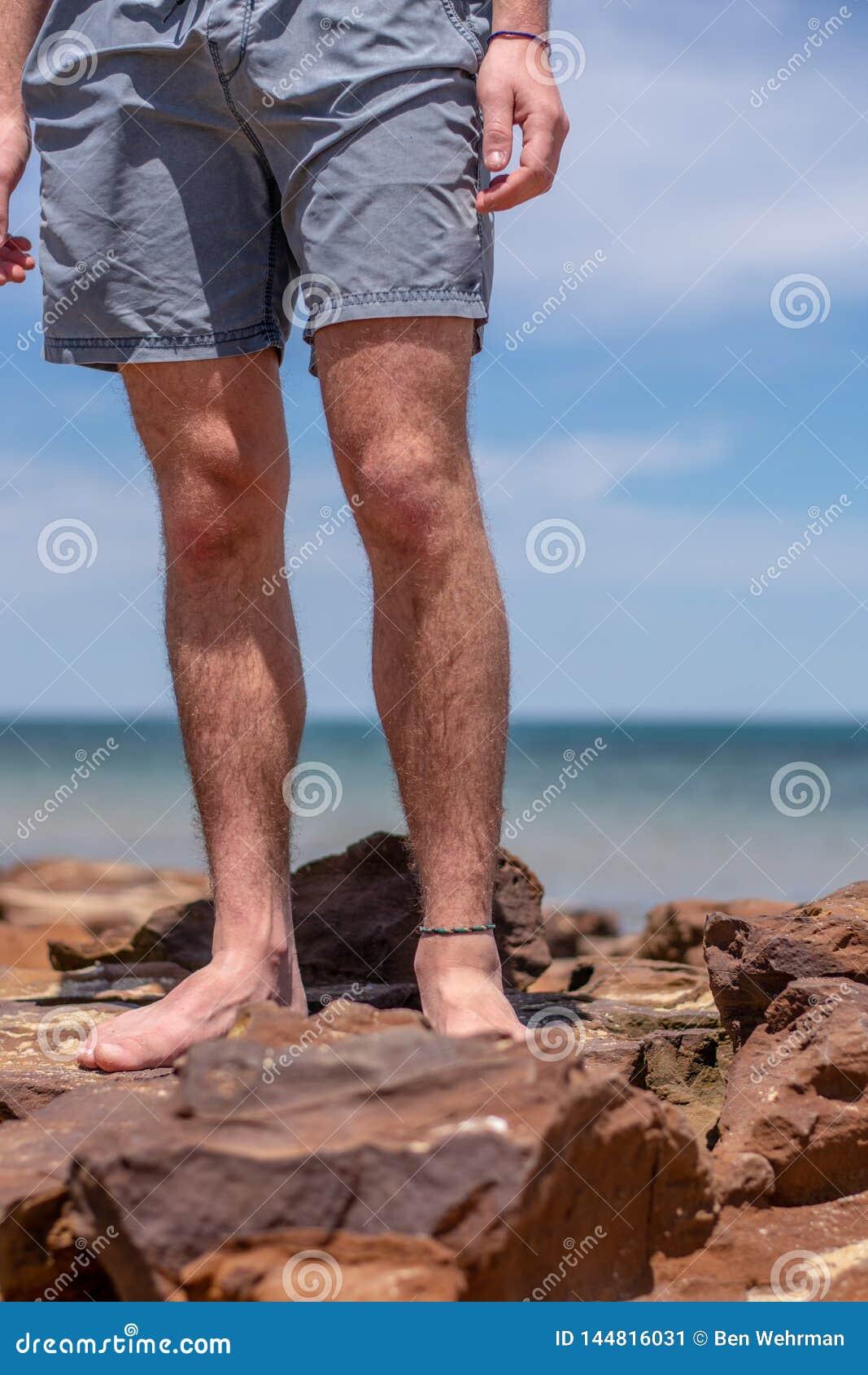 Le gambe del ragazzo sulla spiaggia