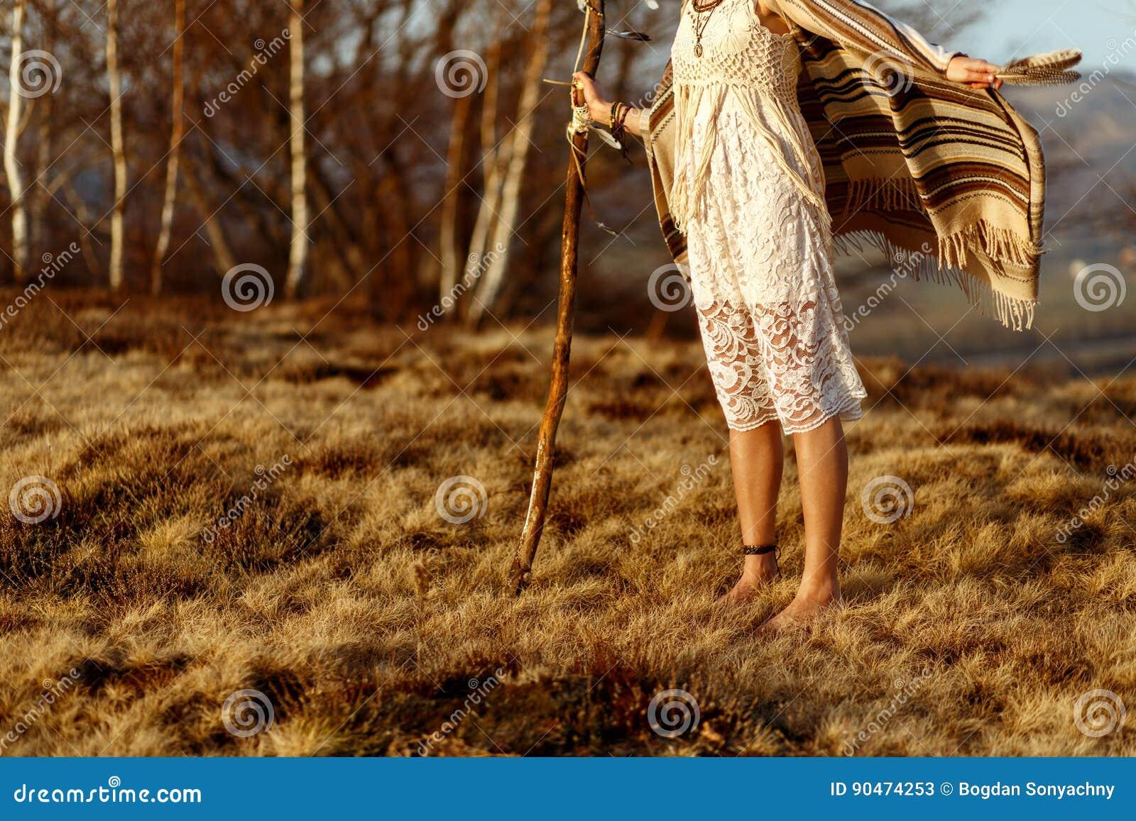 Le gambe della donna in boho americano indiano indigeno vestono la camminata in ventoso