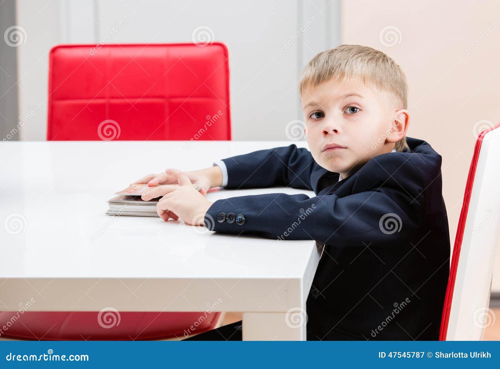 Le garçon à la table avec des photos de plate-forme