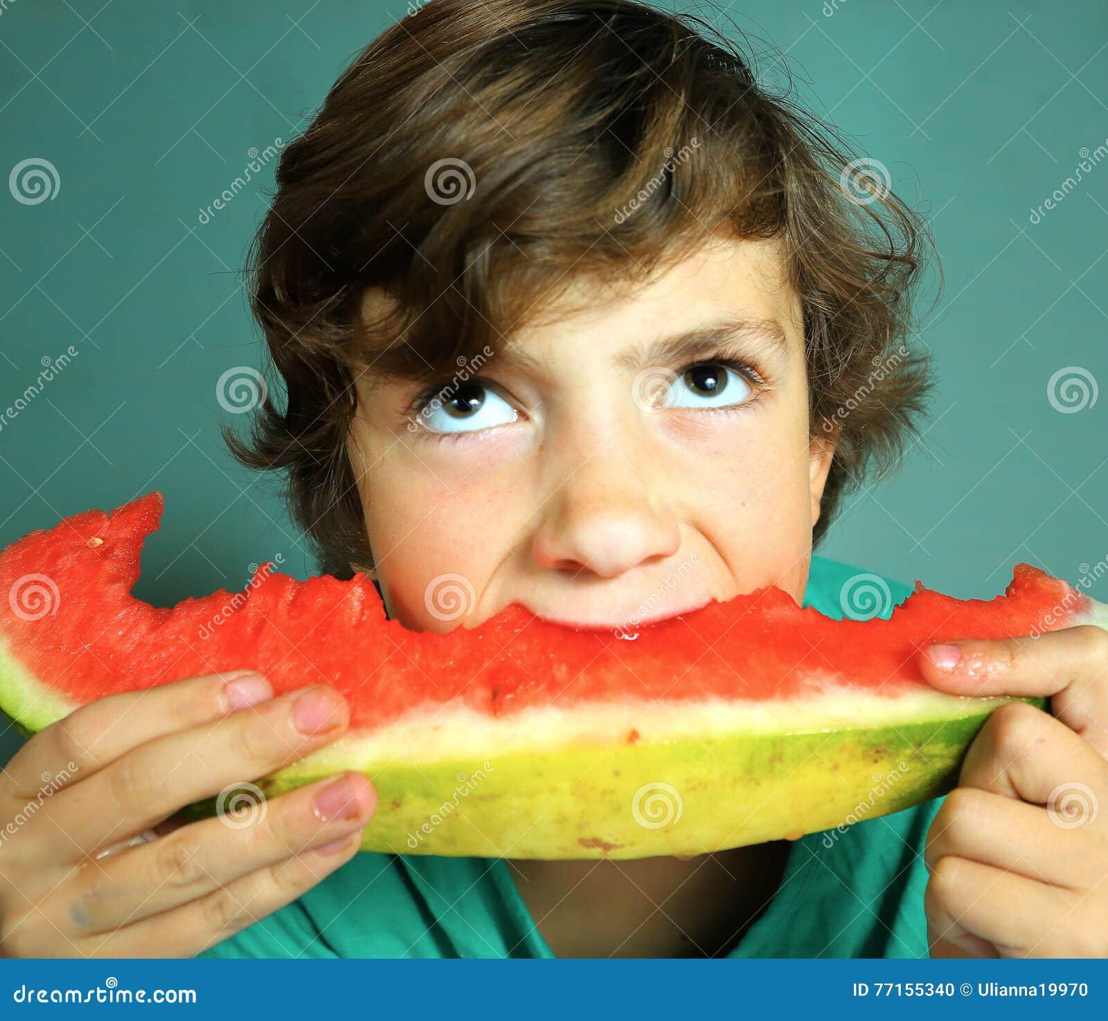 Le garçon beau de la préadolescence mangent la pastèque