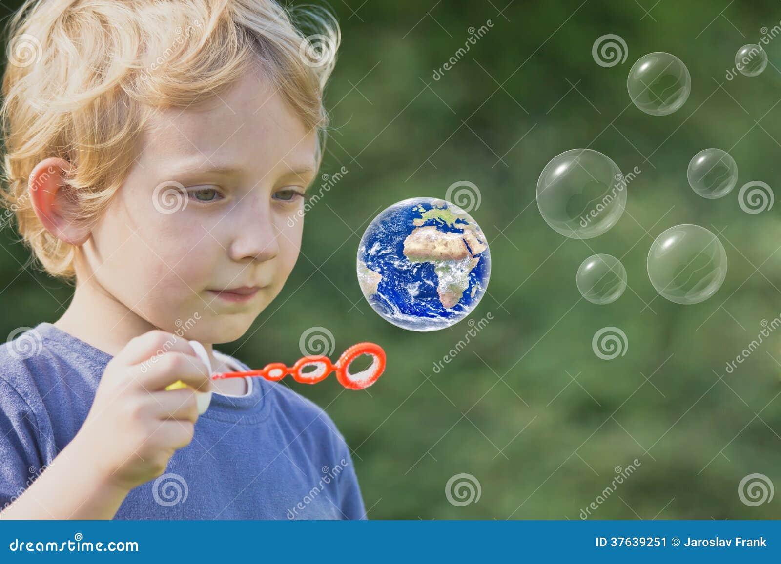 Le garçon blond caucasien joue avec des bulles de savon