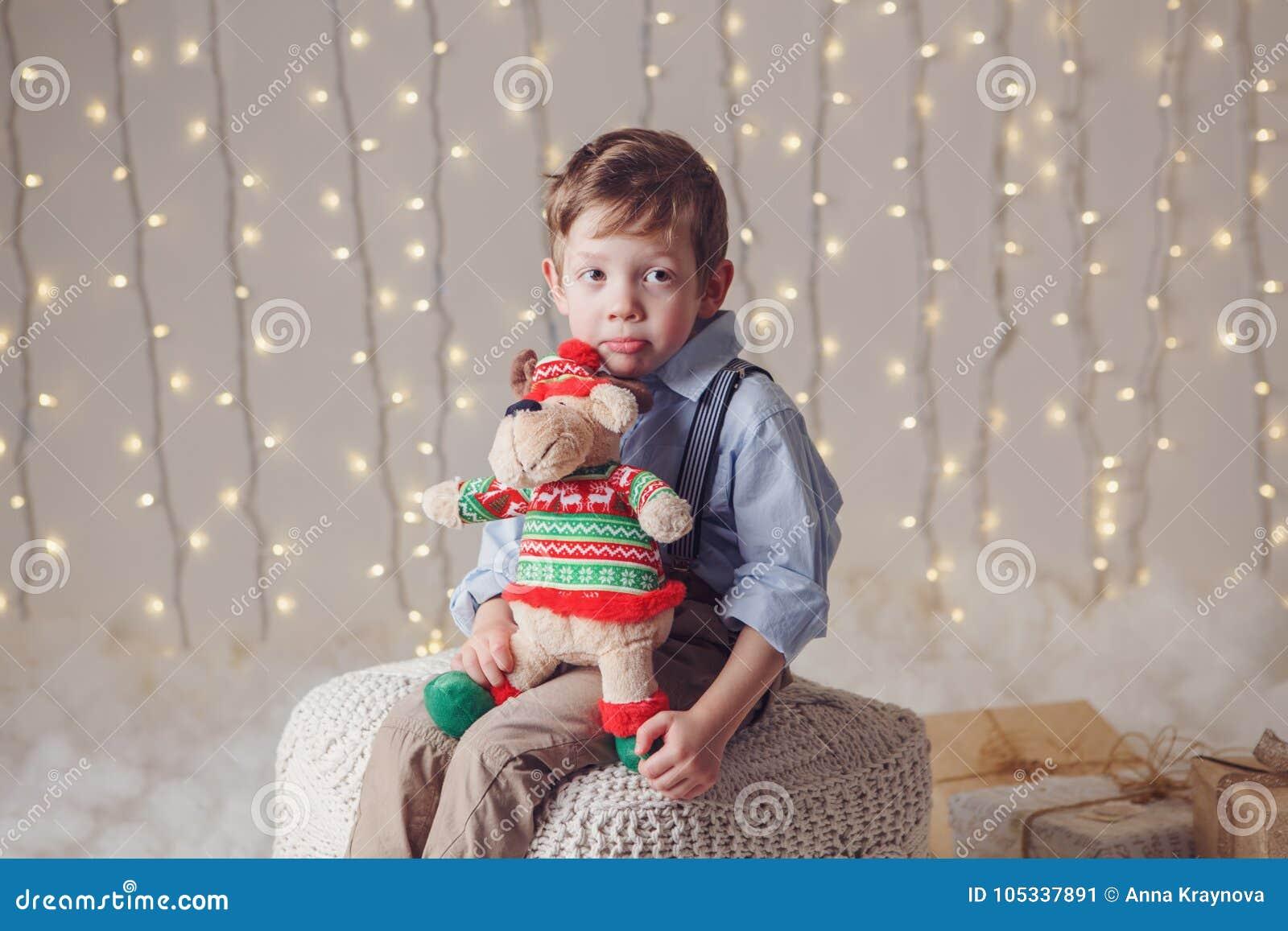 Le garçon caucasien blanc de renversement triste tenant des orignaux de cerfs communs jouent célébrer Noël ou la nouvelle année
