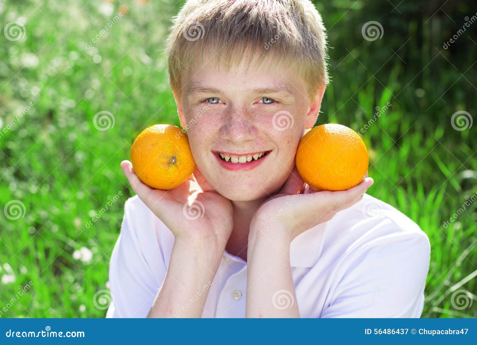Le garçon d adolescent tient deux oranges