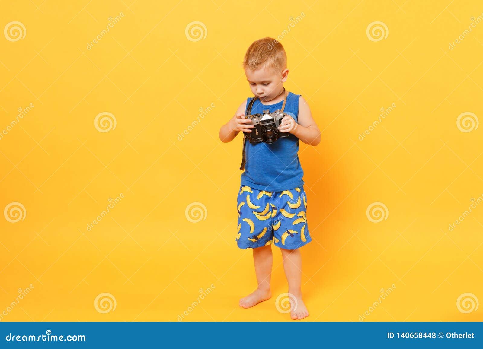 Le garçon d enfant 3-4 années dans des vêtements bleus d été de plage jugent la rétro caméra d isolement sur le fond jaune-orange