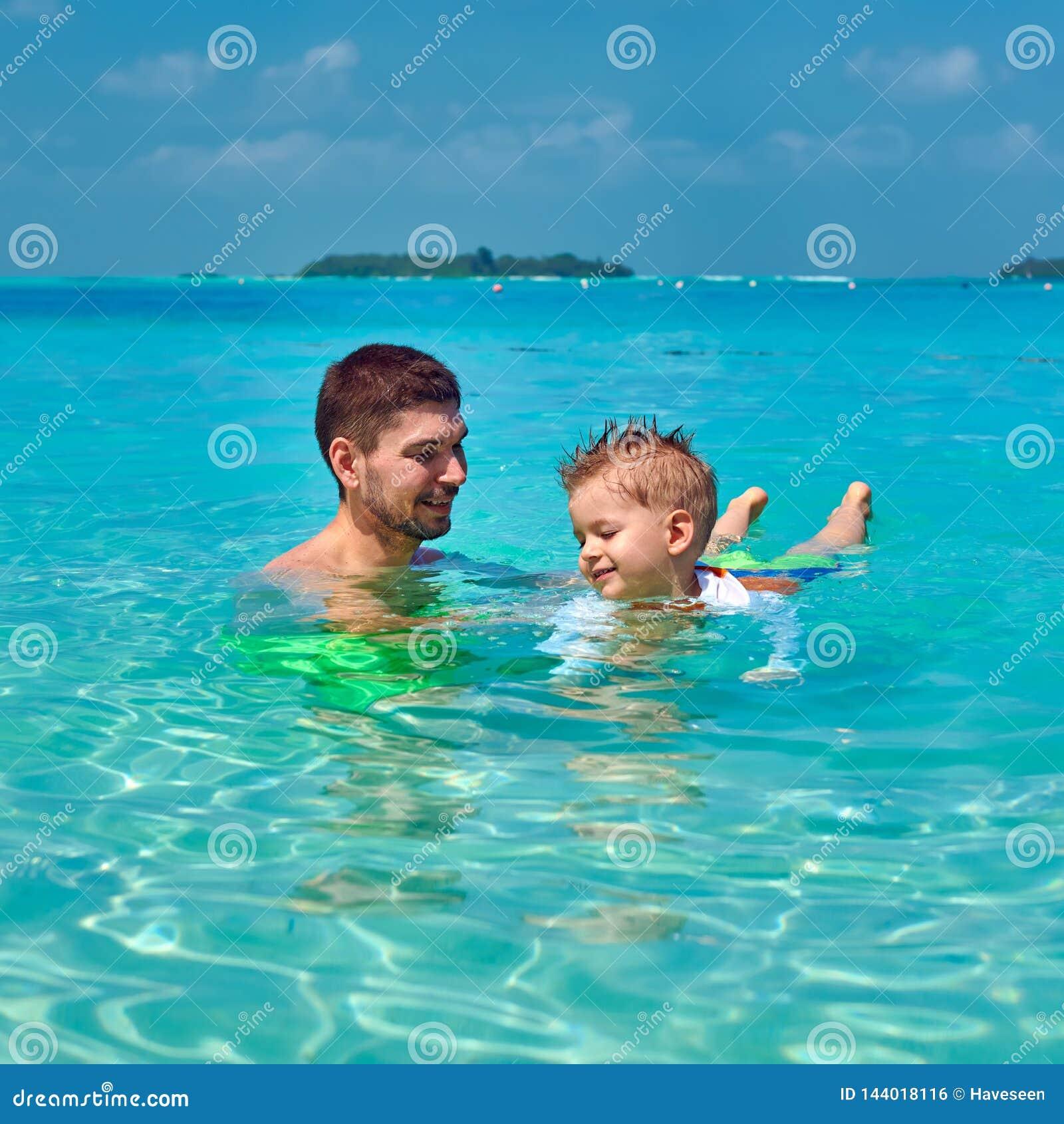 Le garçon d enfant en bas âge apprend à nager avec le père