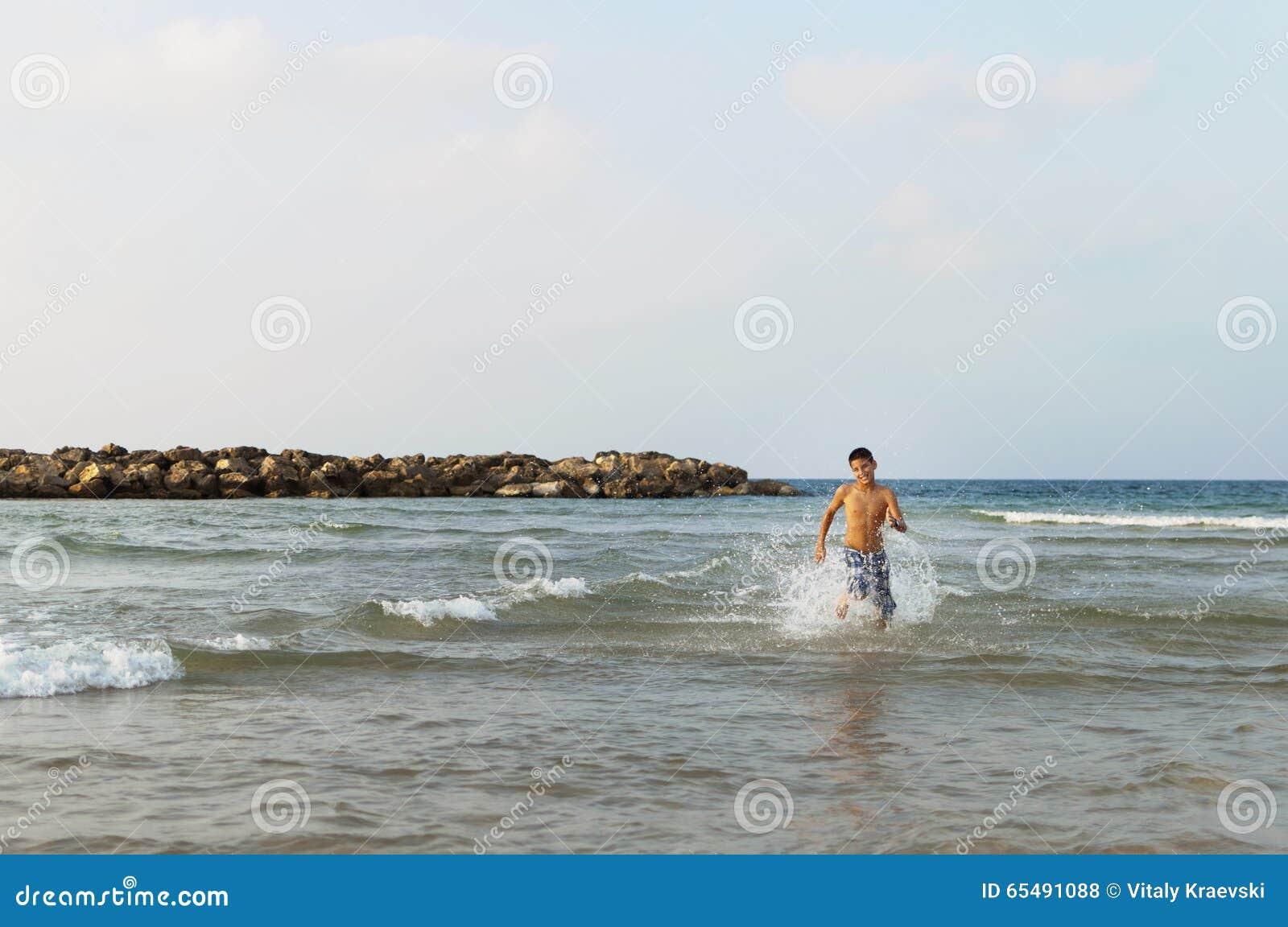 Le garçon de l adolescence court le long de la plage