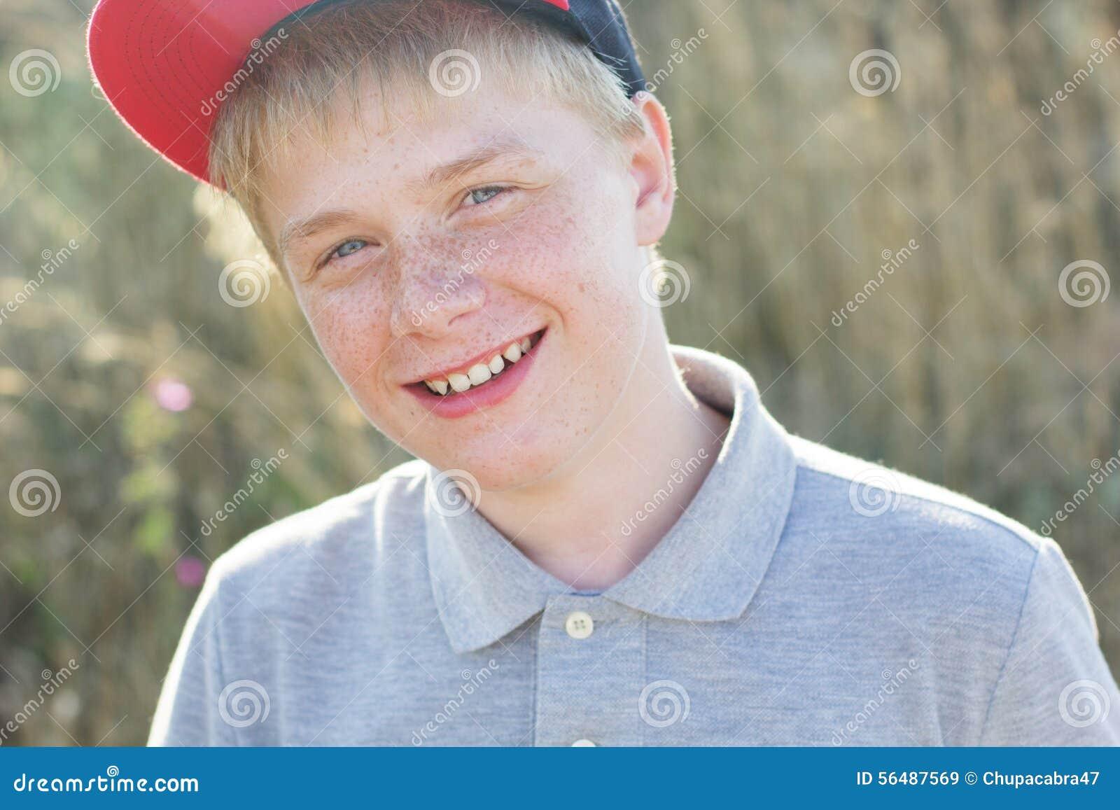 Le garçon de sourire mignon avec des taches de rousseur utilise le chapeau