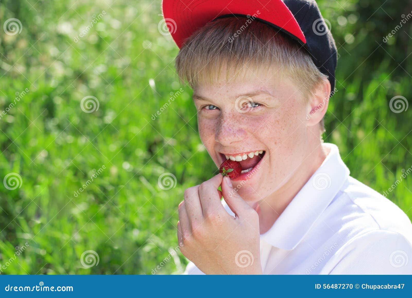 Le garçon de sourire utilise le chapeau rouge mangeant la fraise