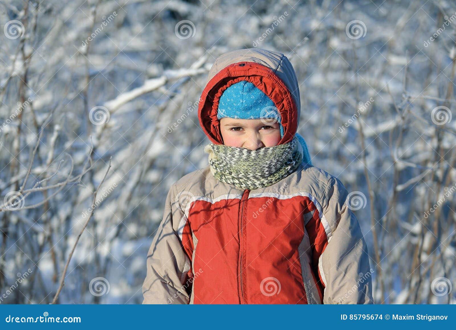 Le garçon dehors dans le jour solaire et très froid