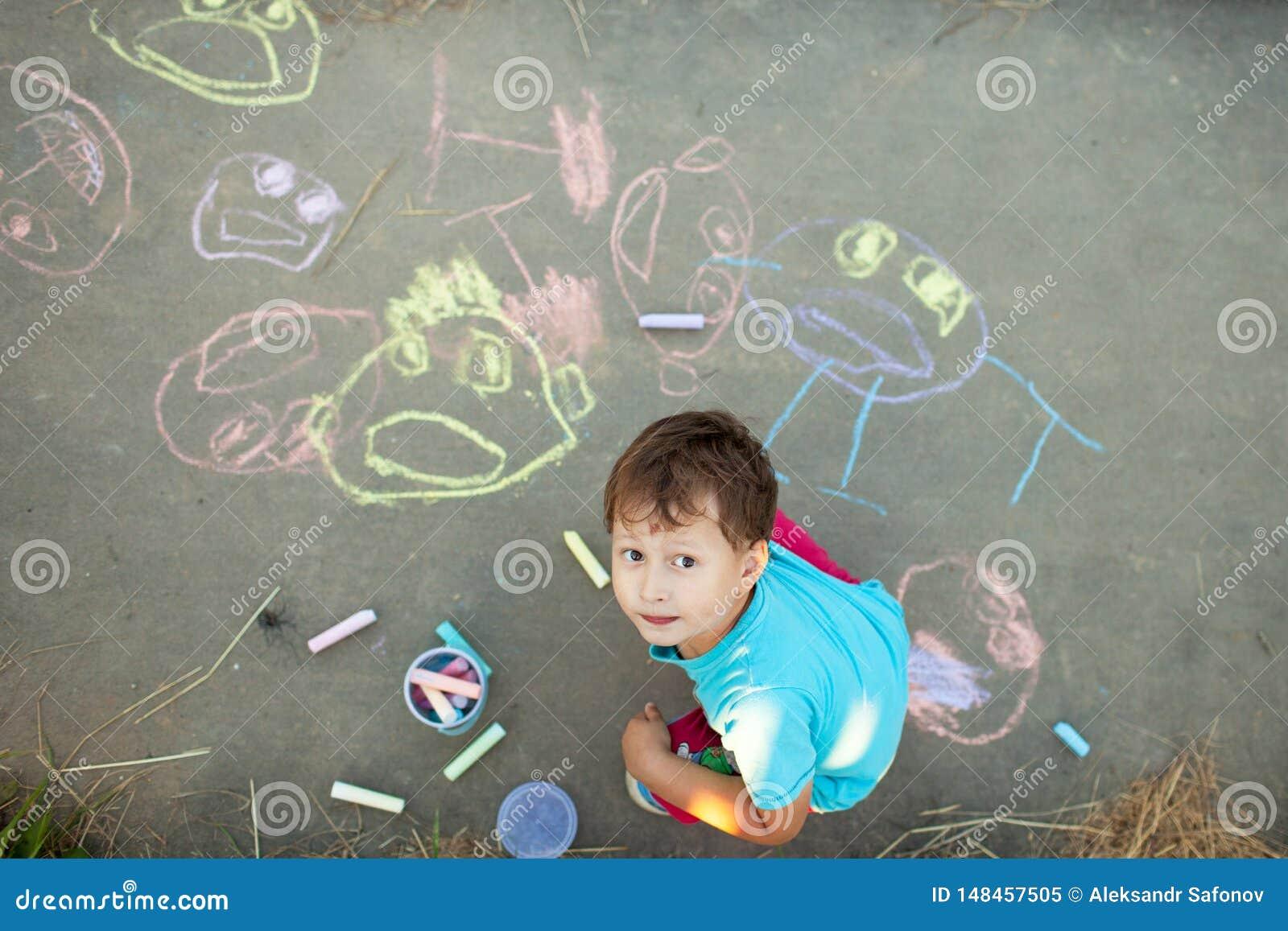 Le garçon dessine avec la craie sur le trottoir