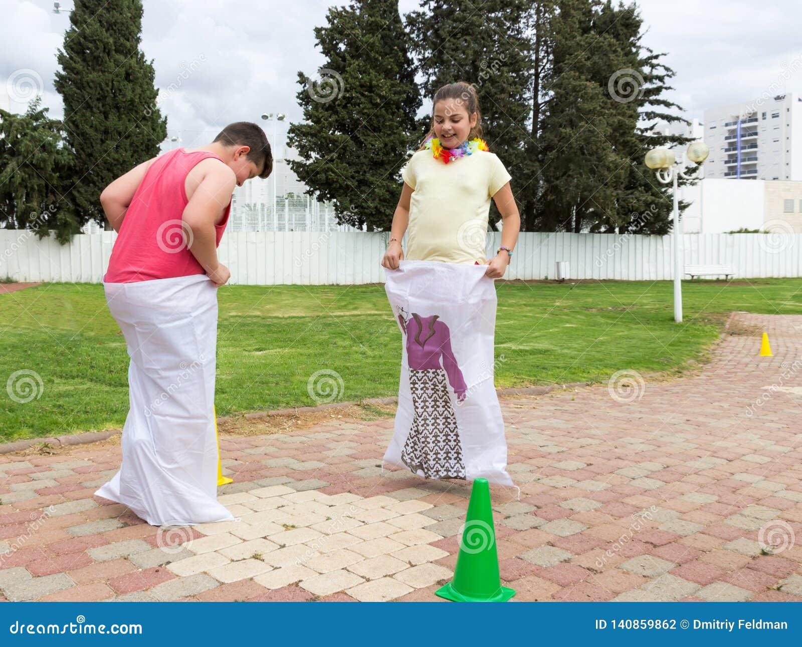 Le garçon et la fille concurrencent en sautant dans les sacs en parc public à Nahariya, Isarel