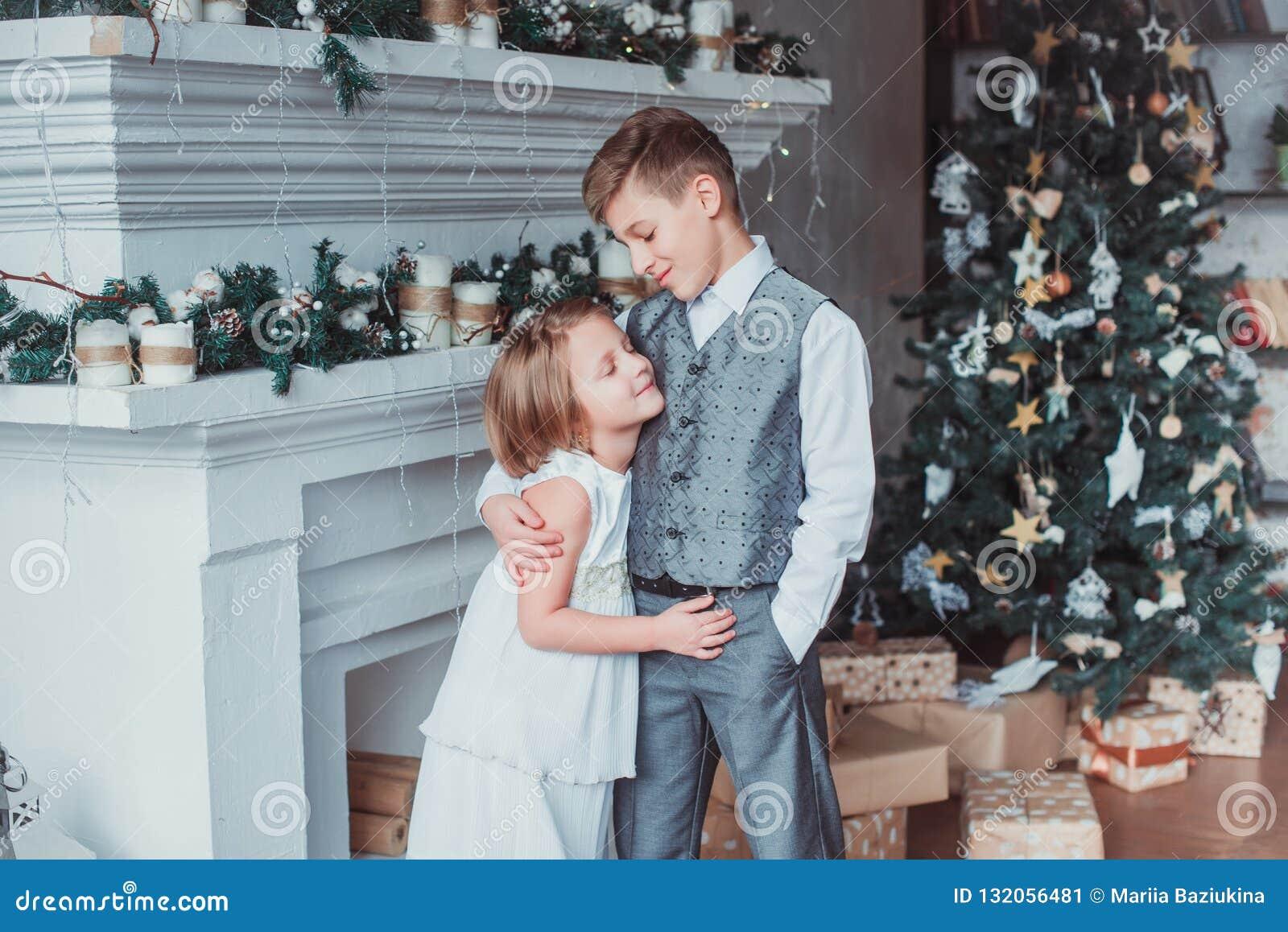 Le garçon et la fille ont habillé d une manière élégante la position dans une salle lumineuse par la cheminée Arbre de Noël à l a