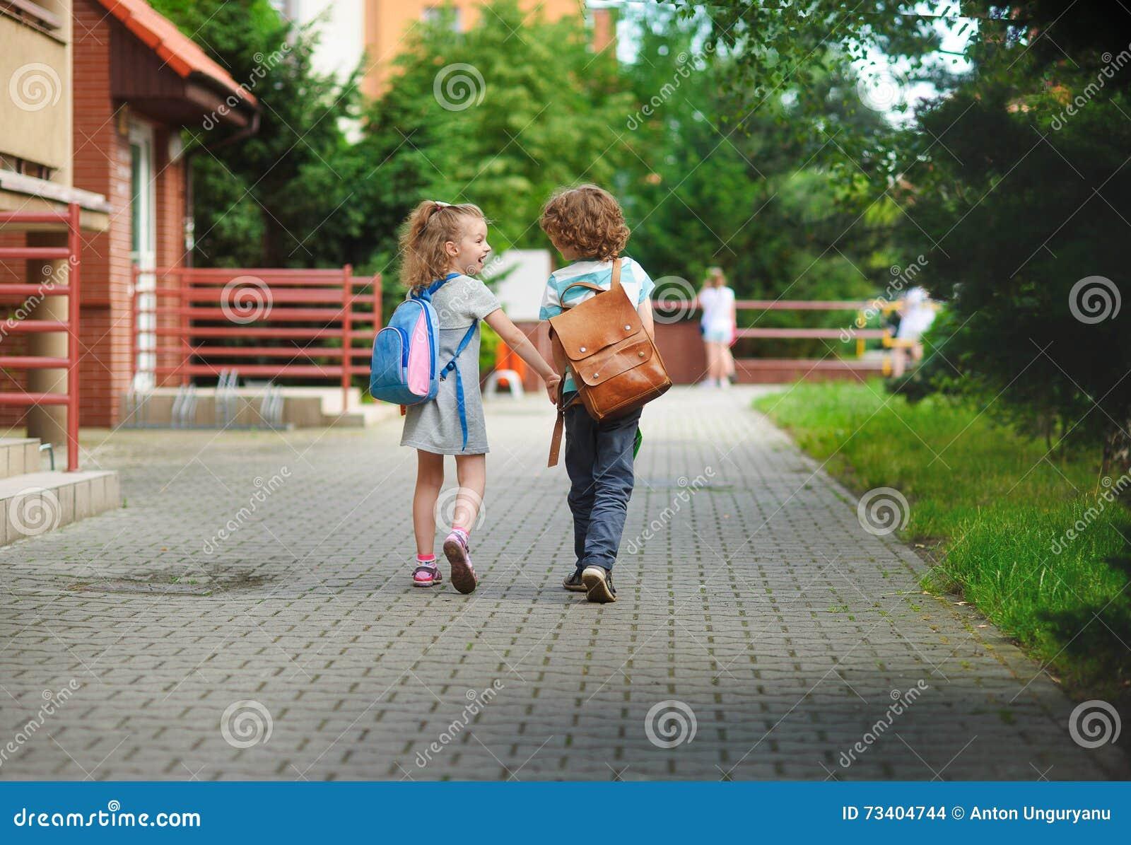 Le garçon et le gerlie vont à l école ayant joint des mains