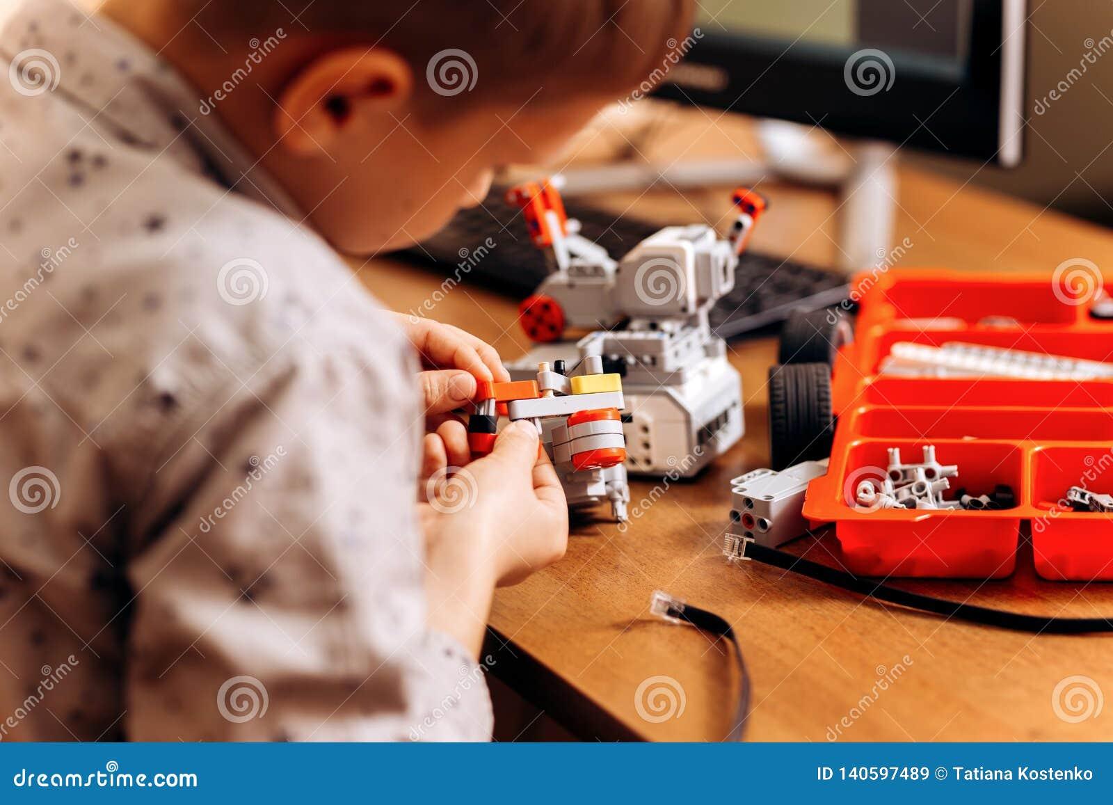 Le garçon futé habillé dans la chemise grise fait un robot à partir du constructeur robotique au bureau dans l école de la roboti
