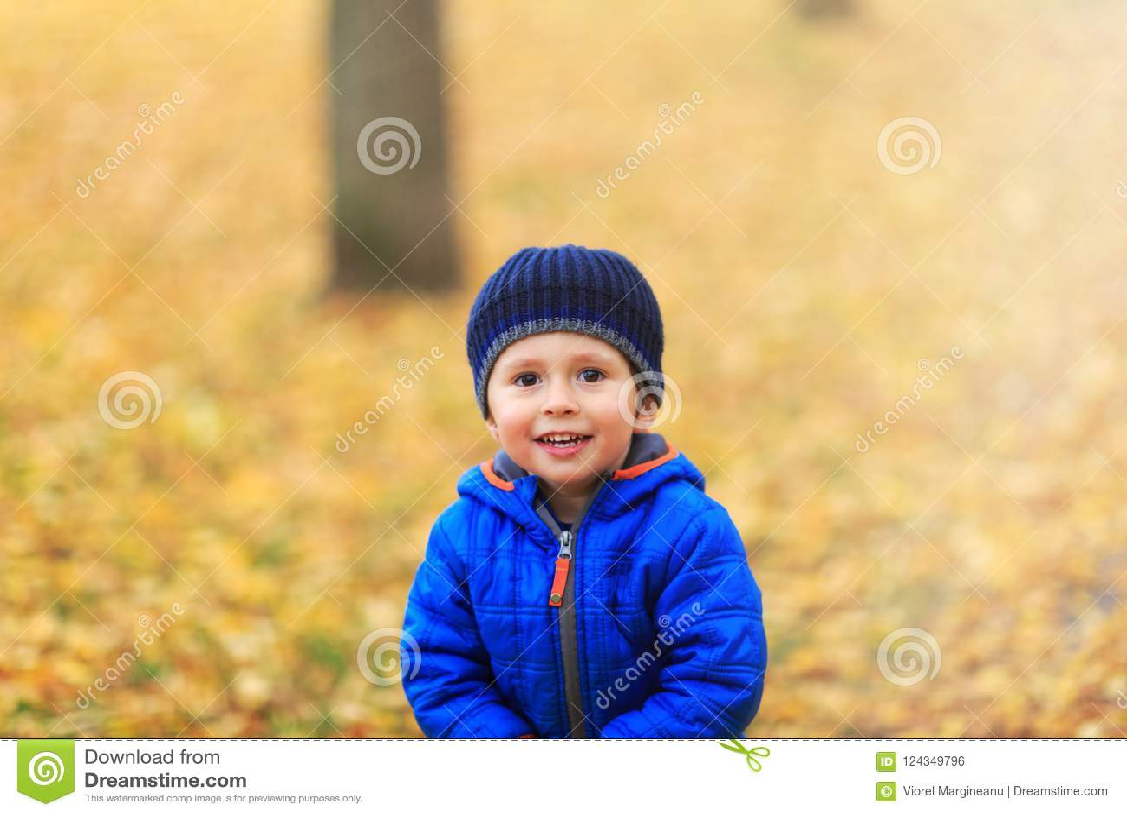 Le garçon heureux s est habillé dans des vêtements chauds avec le chapeau et le manteau dans le colo bleu