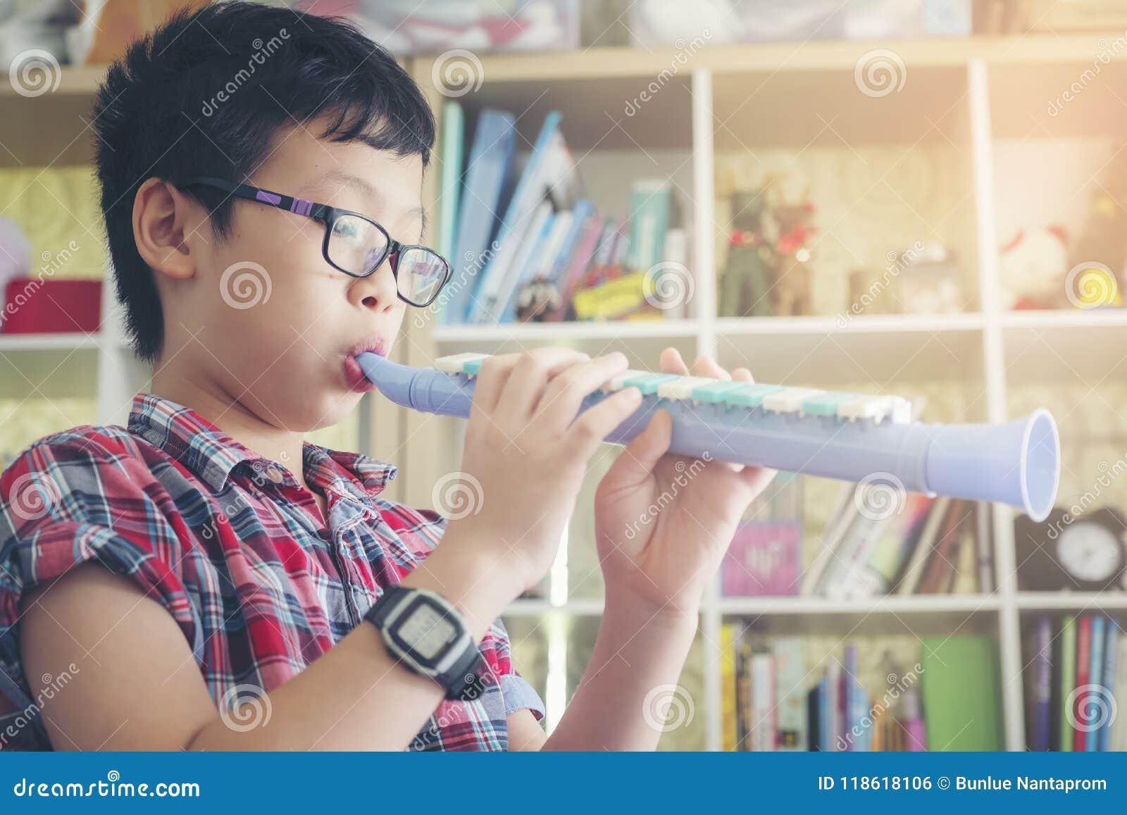 Le garçon jouant la clarinette, sonnent de la trompette à la maison, soufflant une cannelure douce