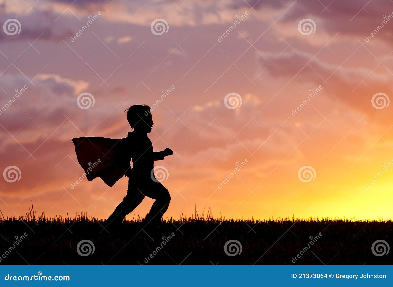Le garçon joue le héros superbe au coucher du soleil.