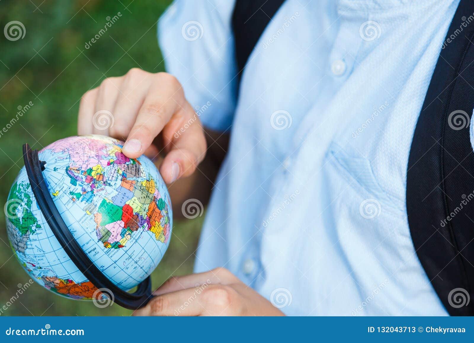 Le garçon mignon et jeune dans la chemise bleue avec le sac à dos et les cahiers tient le globe dans des ses mains devant son éco