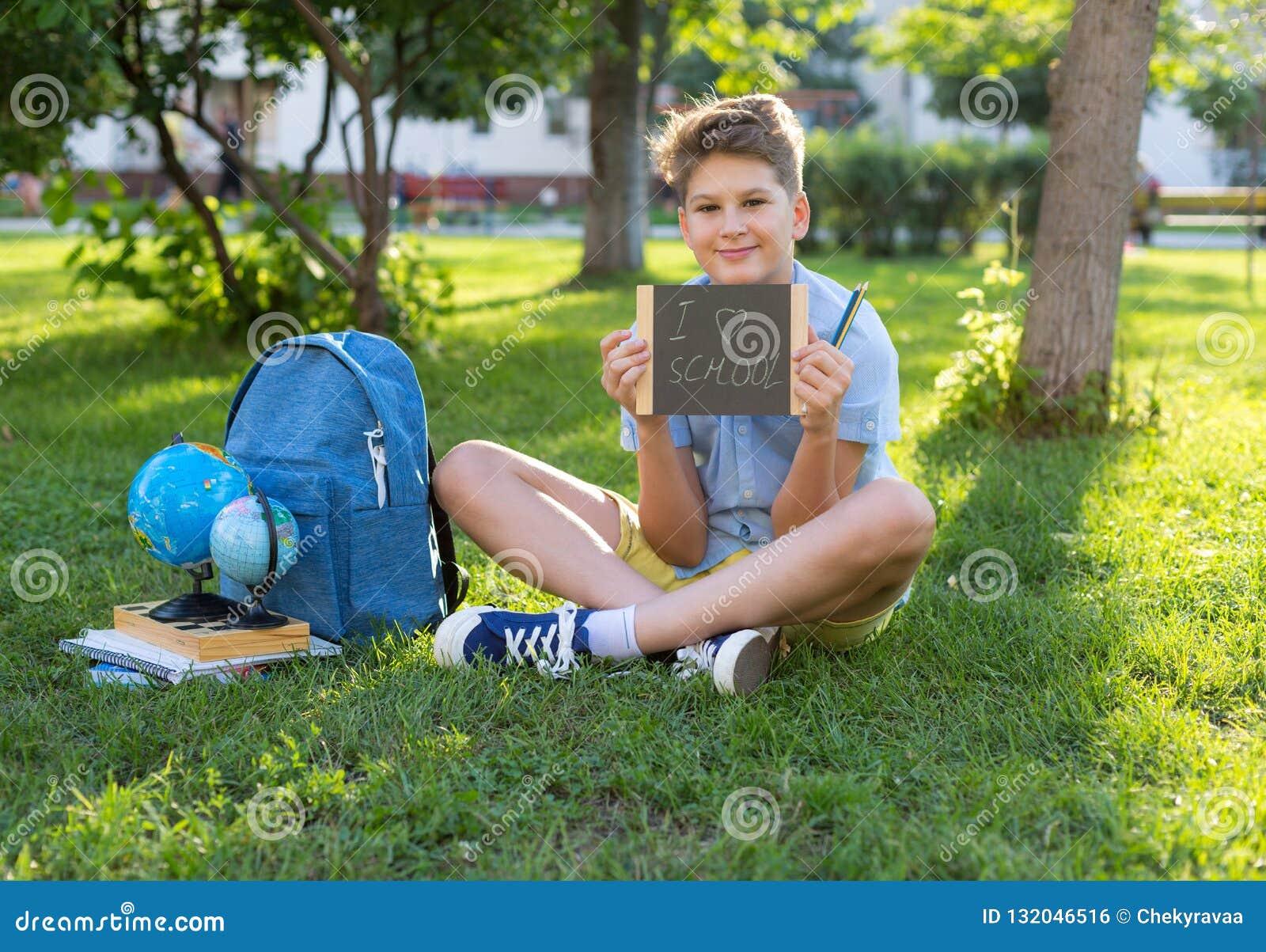 Le garçon mignon, futé, jeune dans la chemise bleue s assied sur l herbe à côté de son sac à dos d école, globe, tableau, cahiers