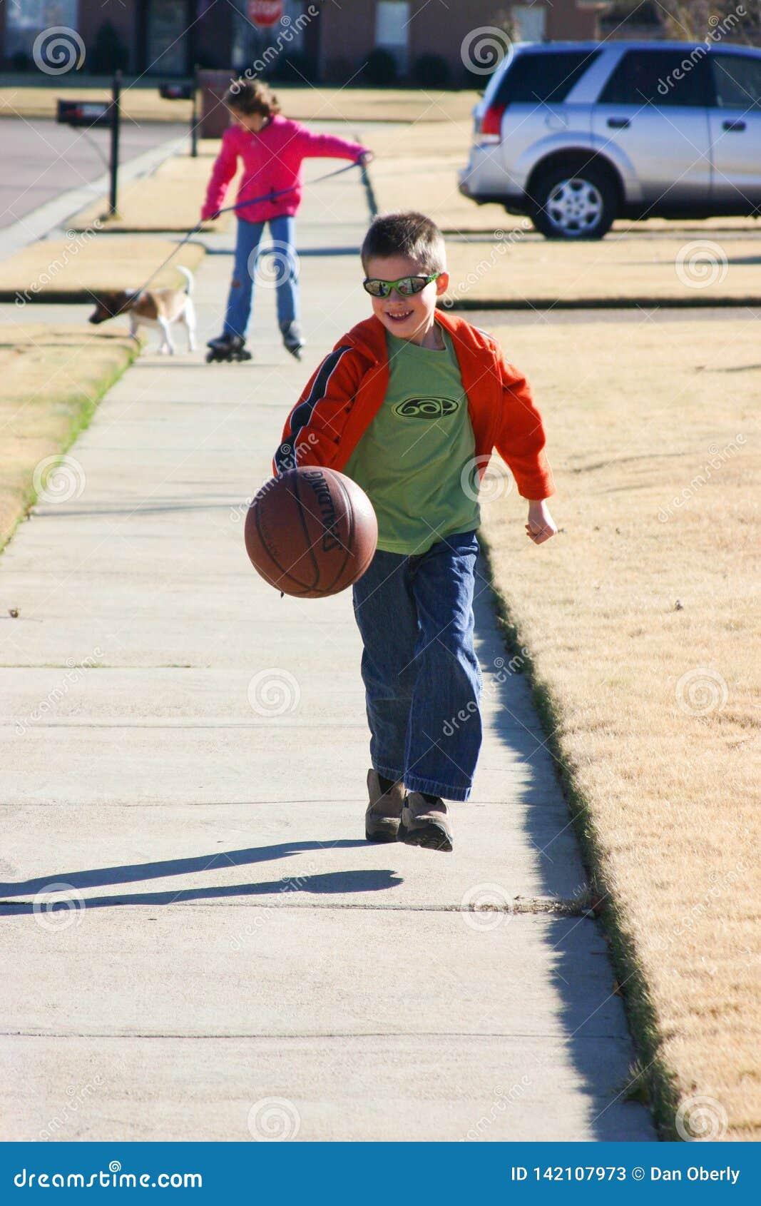 Le garçon a plaisir à rebondir le basket-ball en bas de la rue