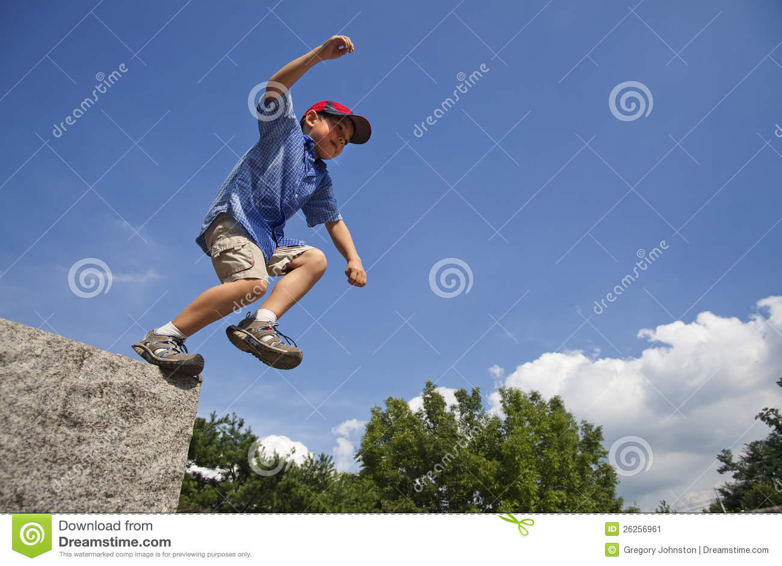 Le garçon saute de la roche.