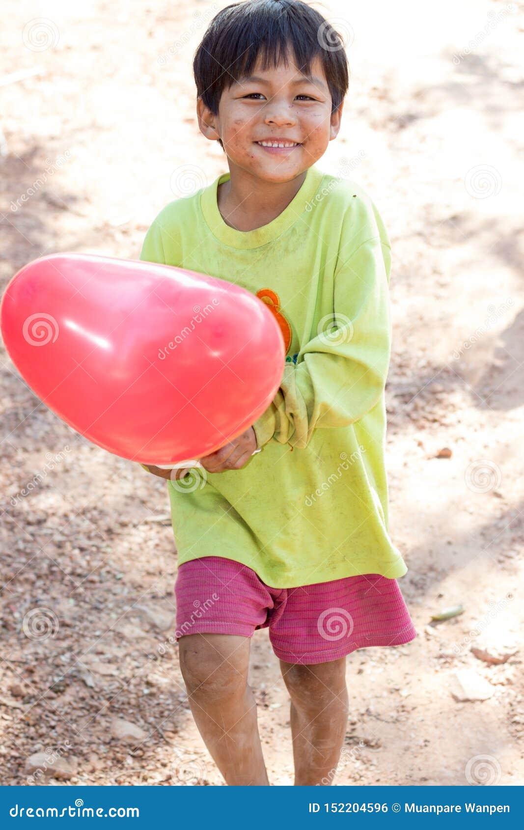 Le garçon sourit dans la main avec un ballon rouge