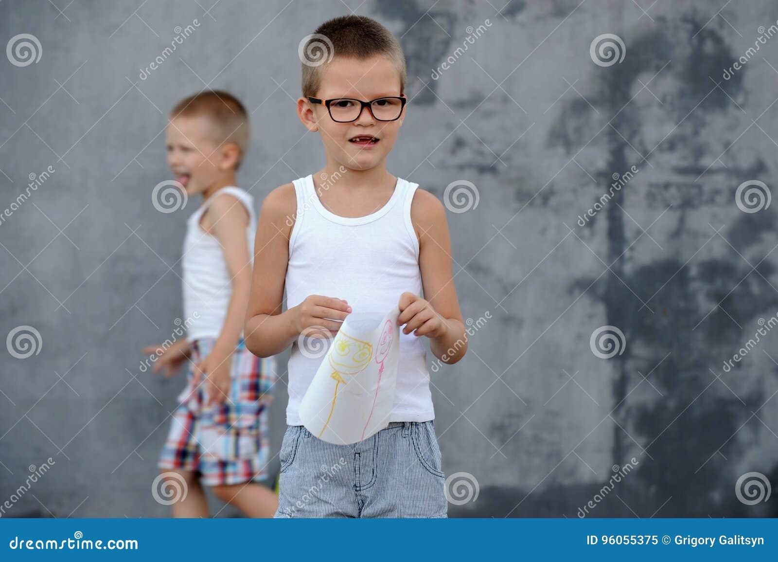 Le garçon supérieur dans une famille nombreuse va à l école et montre ses dessins