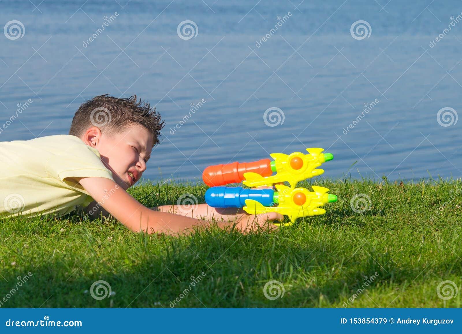 Le garçon, sur le fond d un beau paysage, jouant avec une arme à feu d eau, s ajuste sur la cible, plan rapproché
