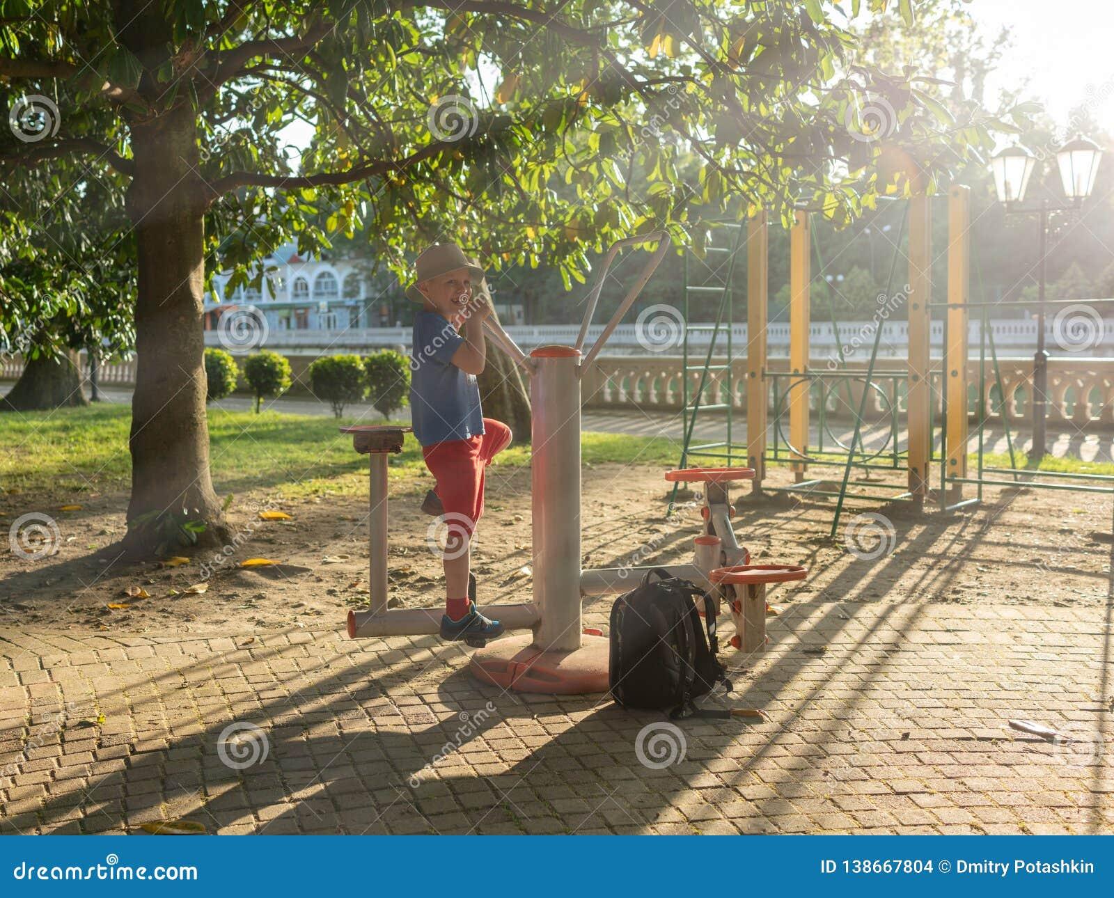 Le garçon va chercher dedans des sports aux sports de rue rectifié dans les rayons du coucher du soleil