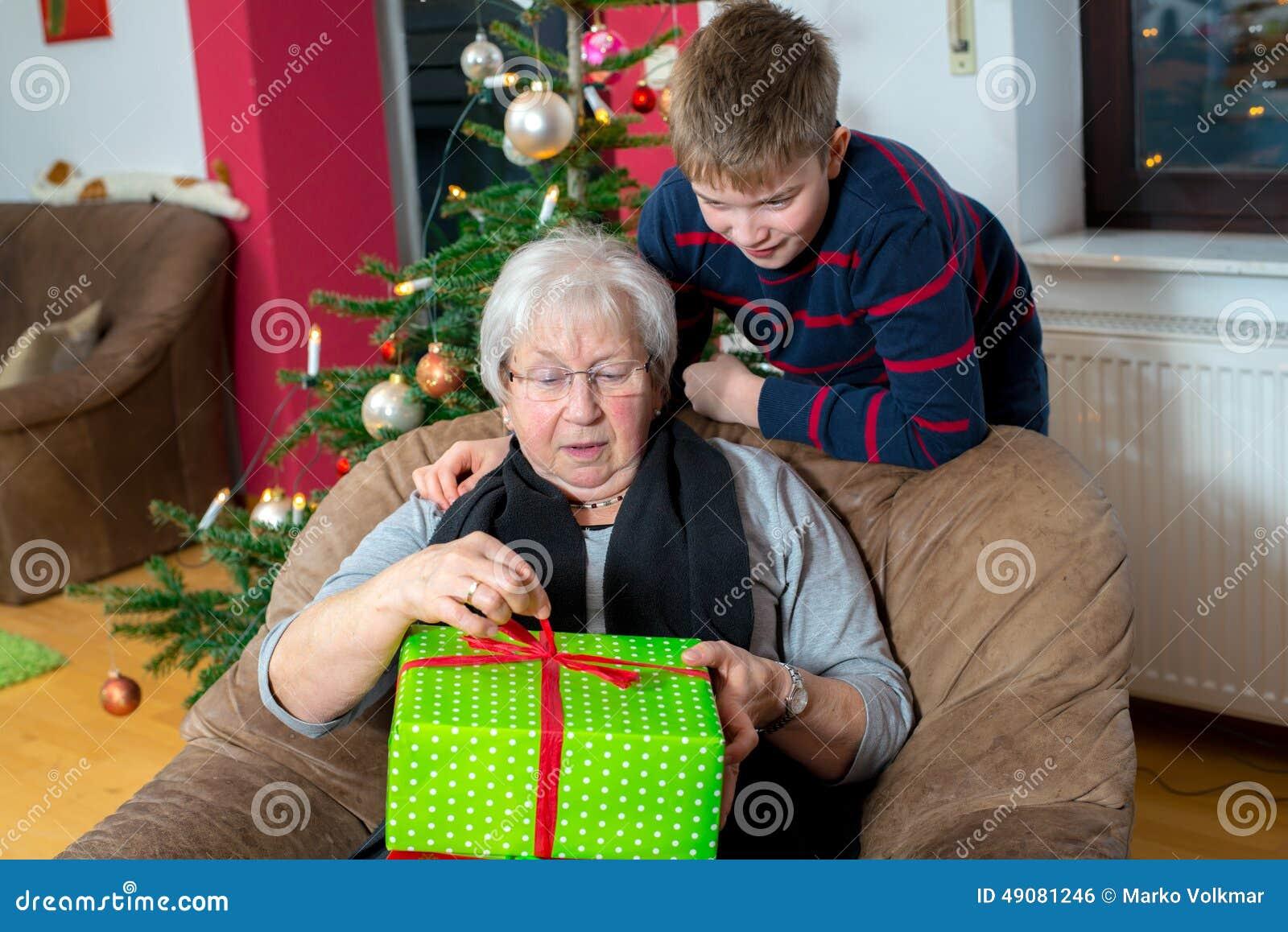 Le gar on a un cadeau de no l pour sa grand m re photo stock image 49081246 - Idee cadeau noel grand mere ...