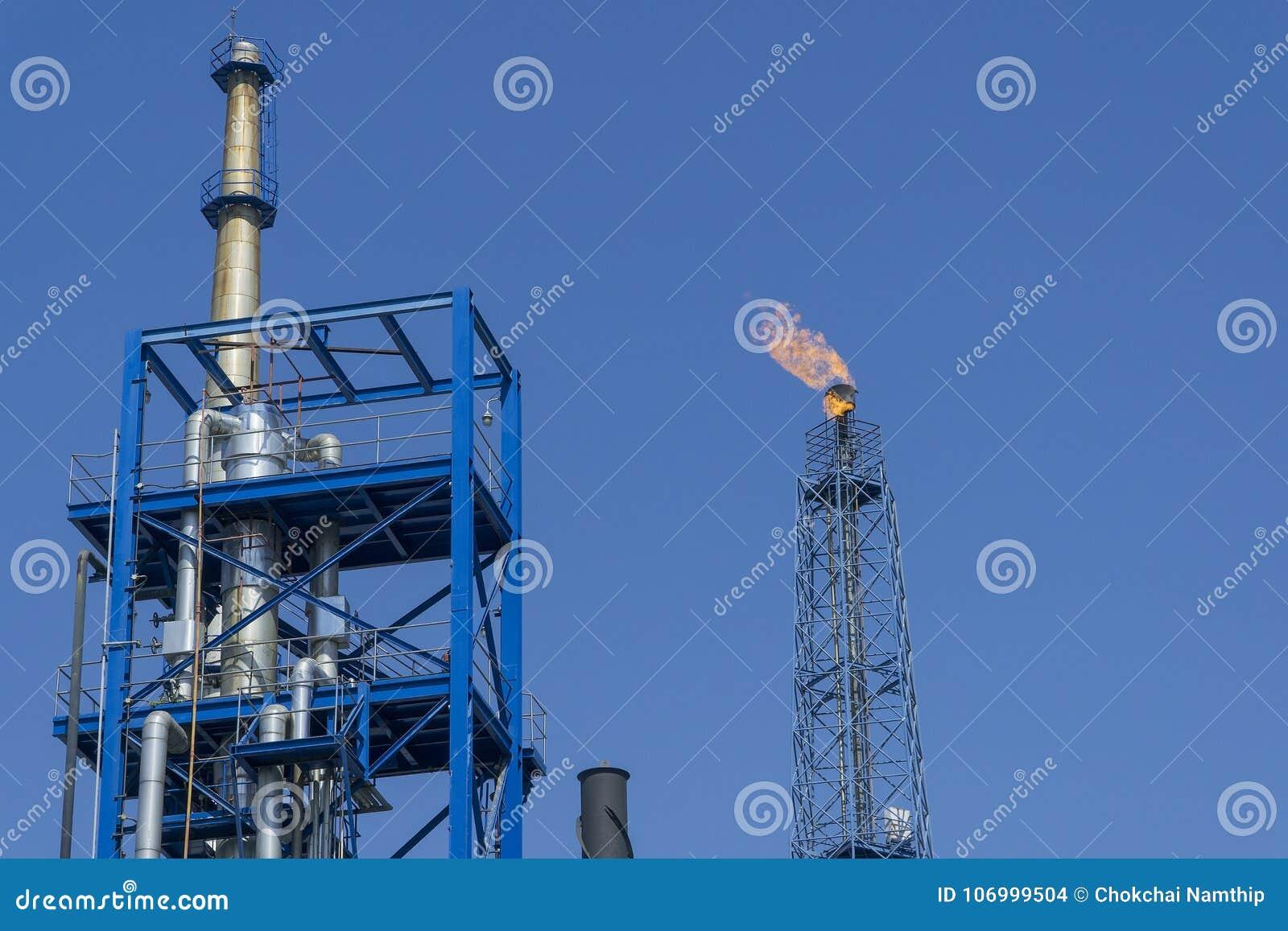 Le gaz évase dans la raffinerie de pétrole avec le fond de ciel bleu