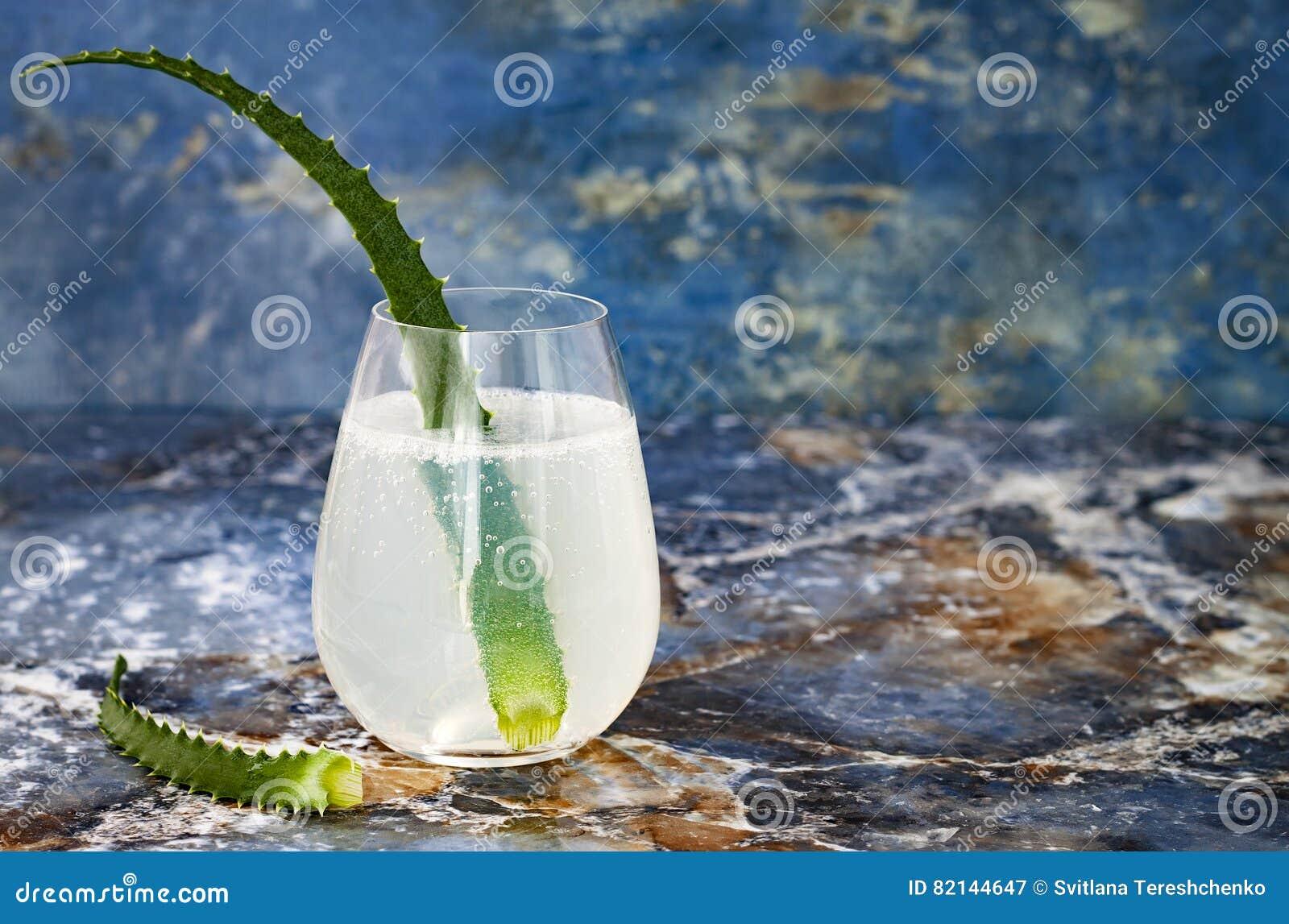 Le genièvre et le tonique en bon état de scintillement de concombre sifflent avec l aloès Vera sur la table de marbre Copiez l es
