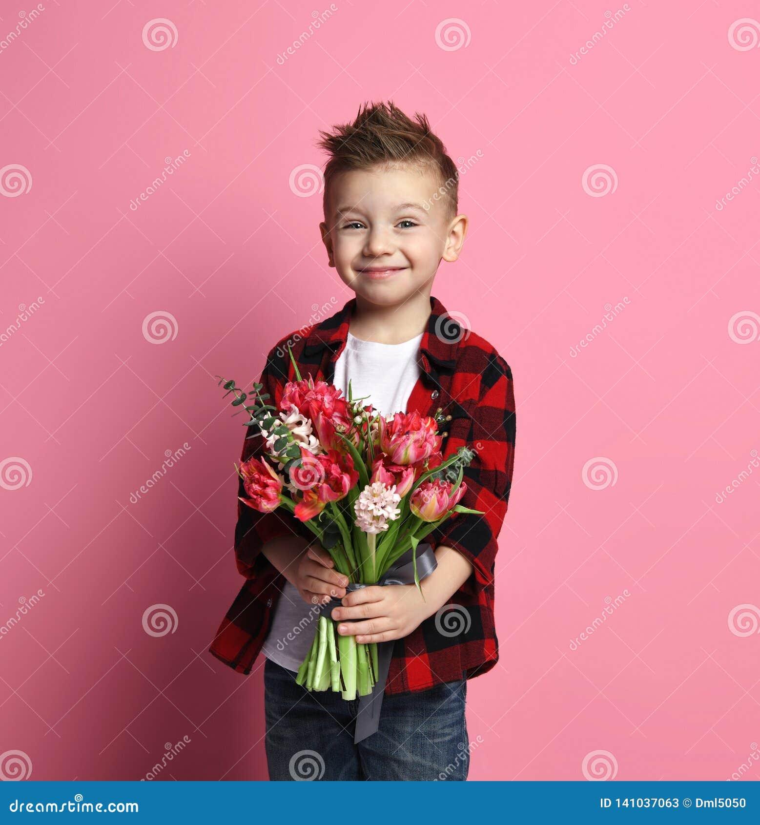 Le gentil enfant de petit garçon dans les blues-jean et la chemise rouge donne un grand bouquet des fleurs de ressort pour un jou