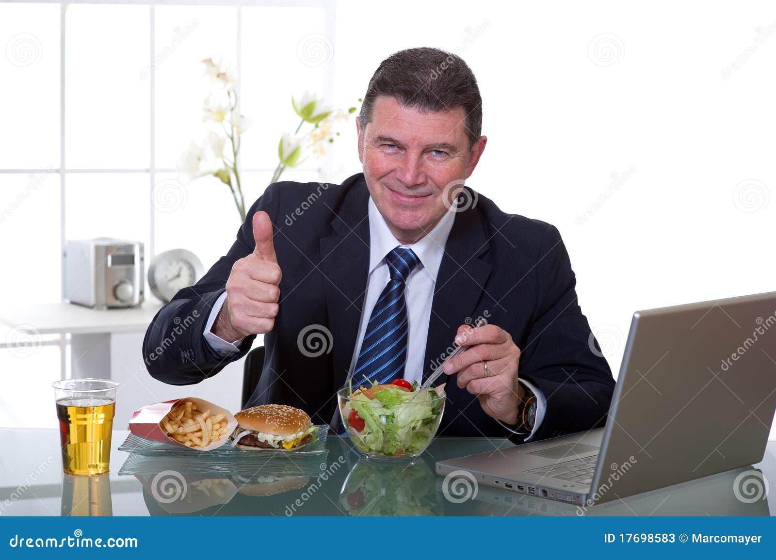 Le gestionnaire au bureau mangent de la salade verte